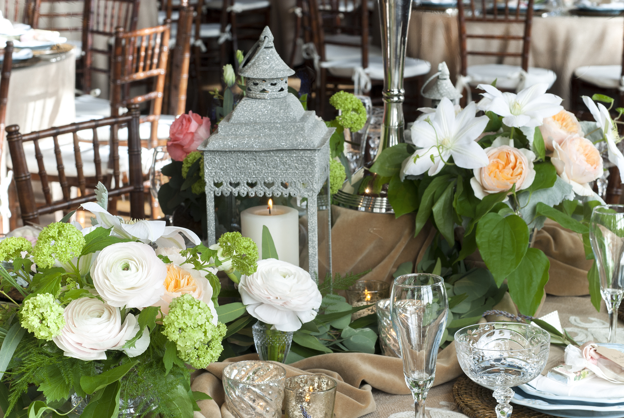 Wedding flowers surround candle lanterns on long reception tables