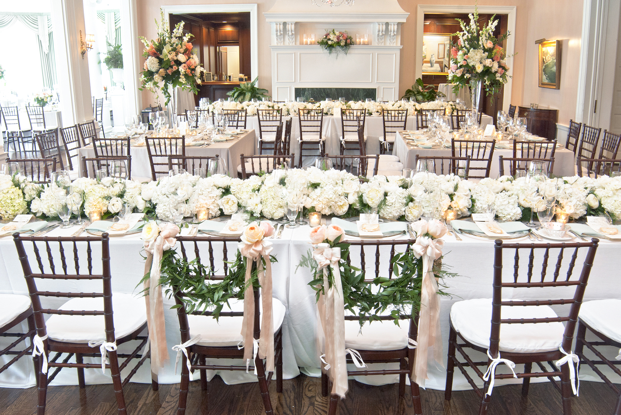 Wedding centerpieces as fresh flower runners for the head table at a club reception