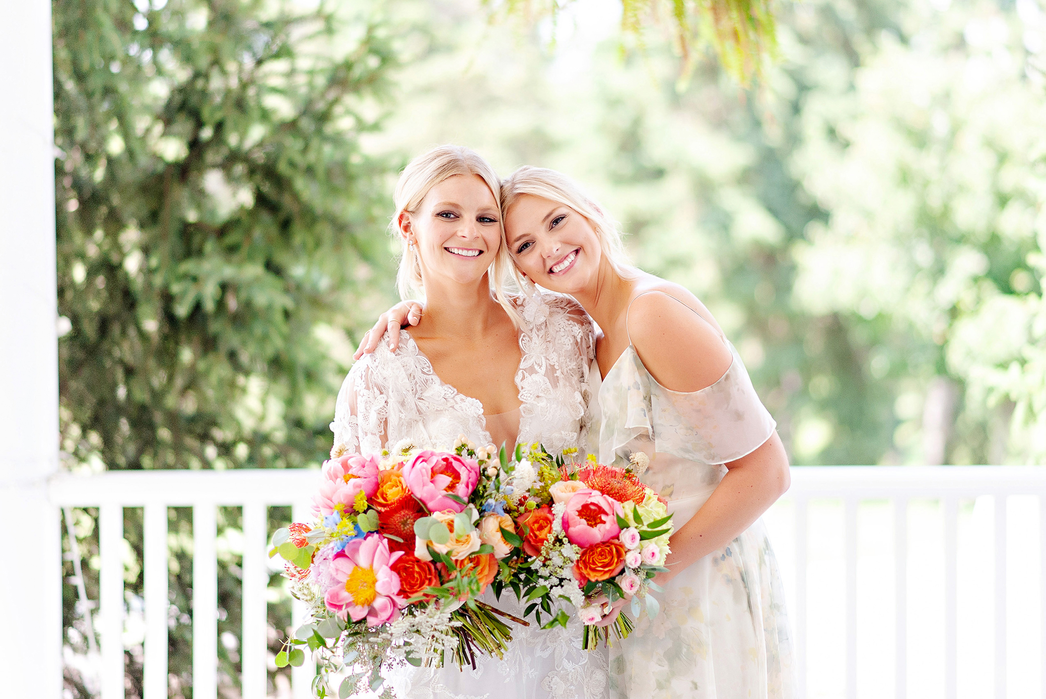 A spring bride and her maid with colorful wedding flower bouquets