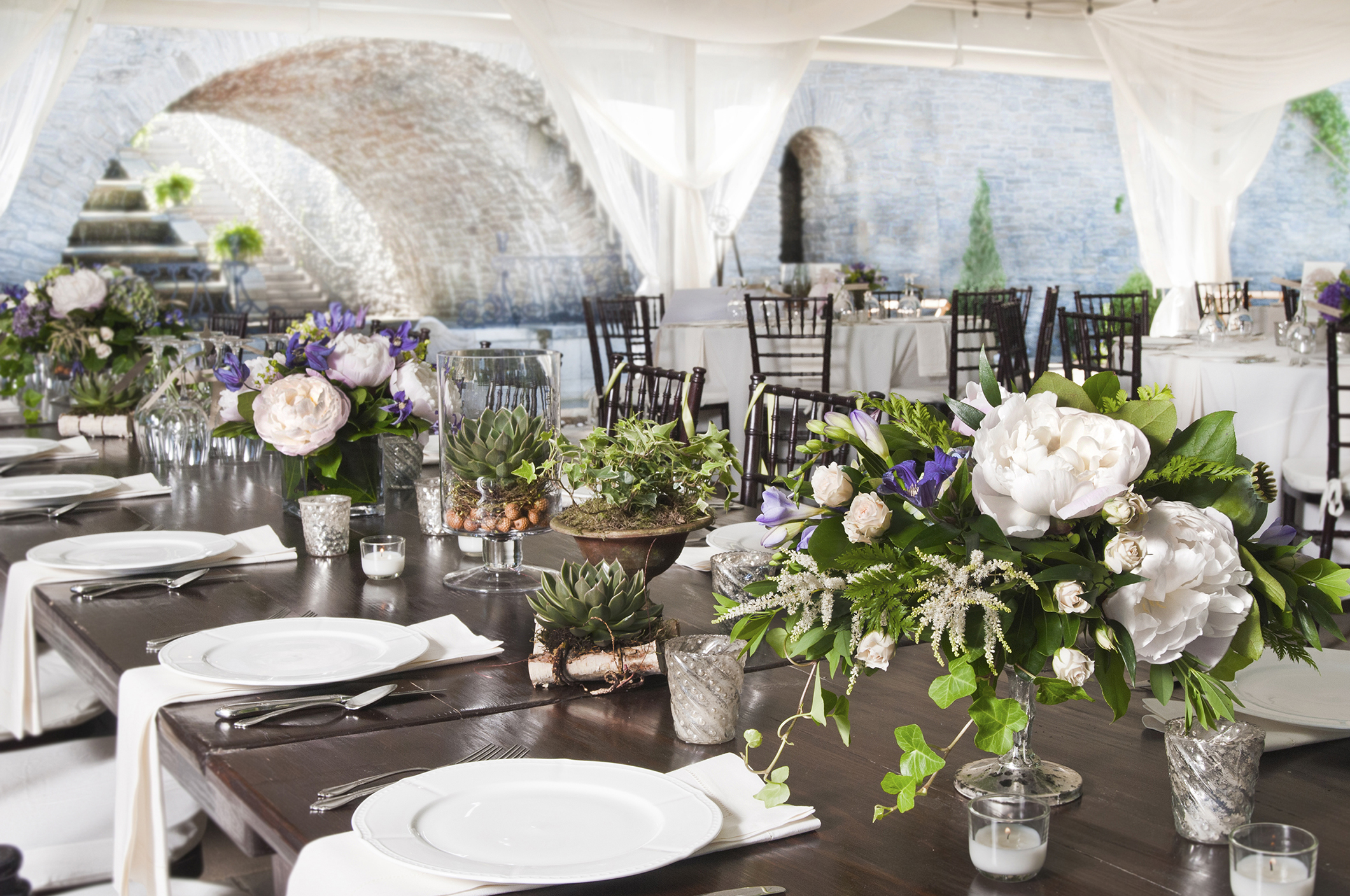 Wedding reception tables with natural peony centerpieces in an outdoor setting