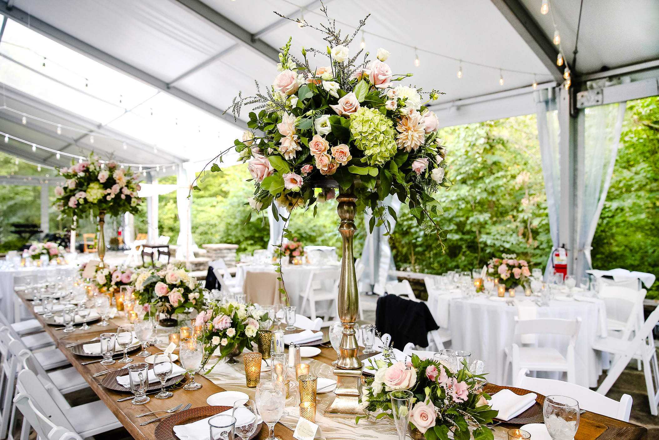 Outdoor wedding reception tables filled with fresh flower centerpieces