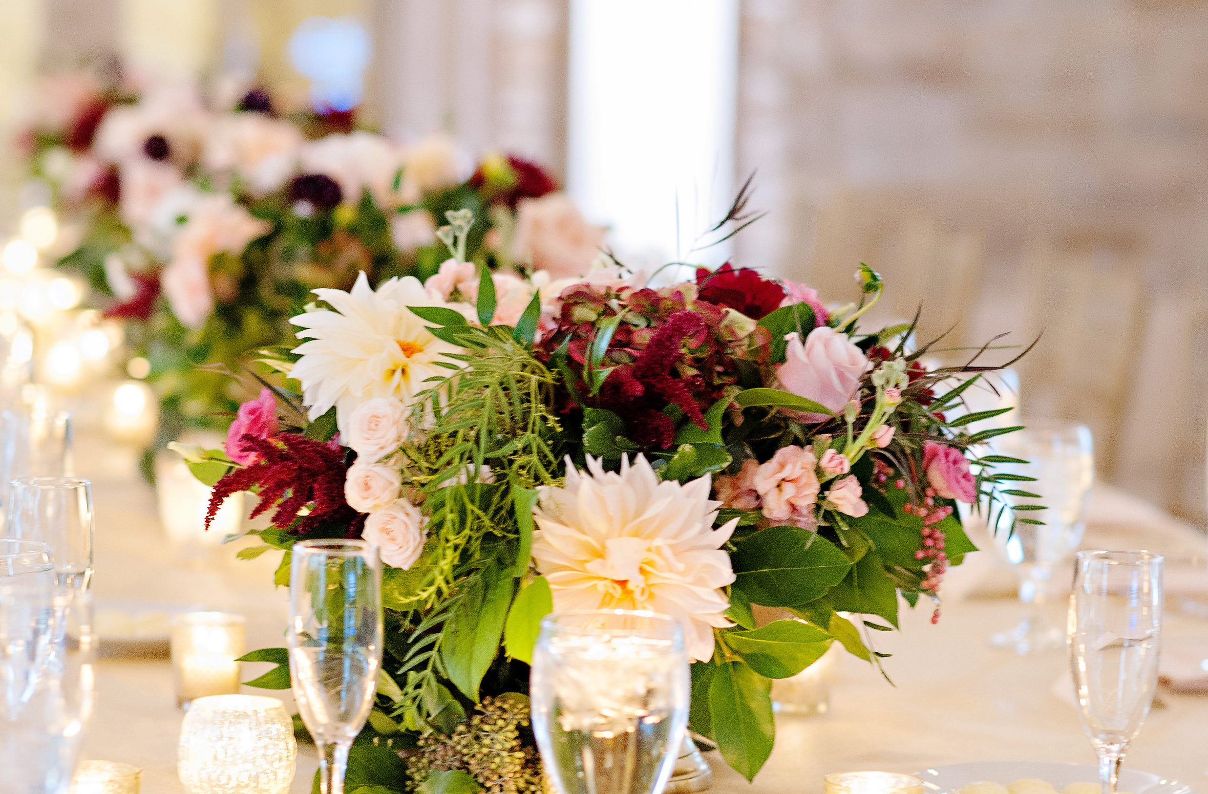 Outdoor wedding table decor of fall flower centerpieces and long garlands. Autumn pastel dahlias with crimson red and burgundy accents, draping berries and foliage, in low pedestal fresh flower arrangements.