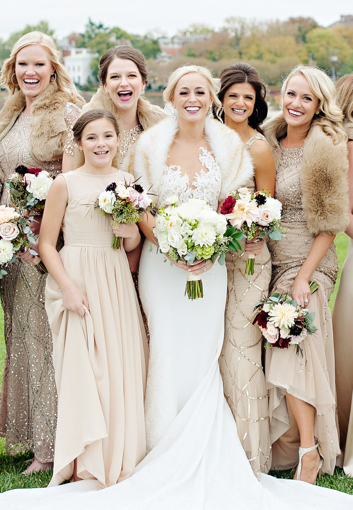 Happy bridal party in blush with rose gold sequin accented bridesmaid dresses and fall pastel wedding bouquets accented by crimson red and burgundy flowers.