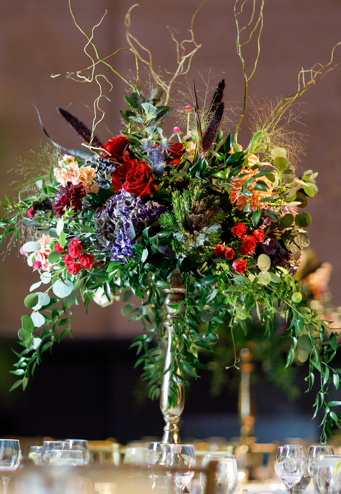 Tall wedding centerpiece in deep colorful autumn flowers and foliage with grasses and willow stems. A close-up view with brass pedestal risers on the reception tables for unique floral inspiration.