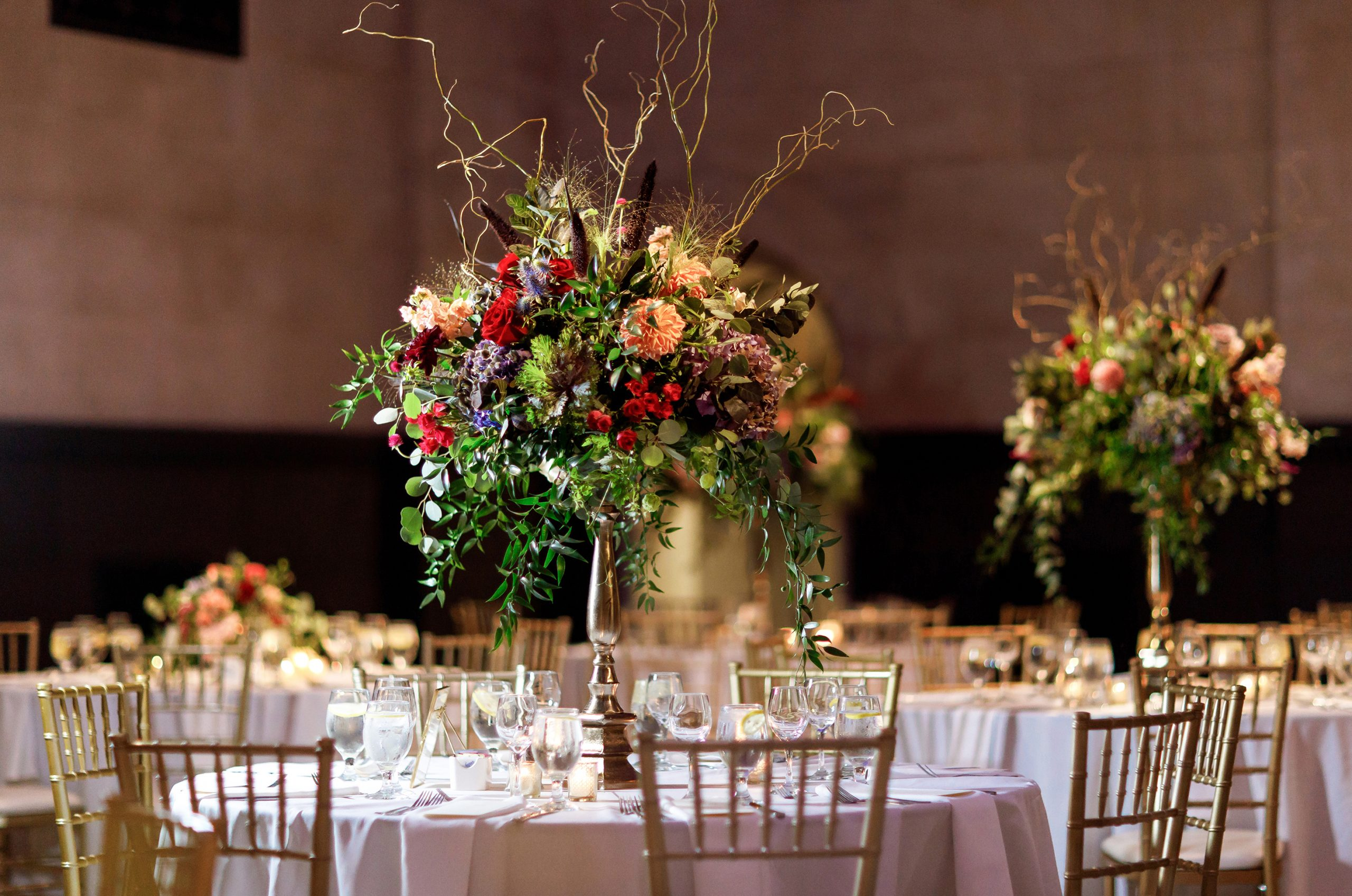 Striking tall floral centerpieces in rich fall colors rise above the tables set for the wedding reception, surrounded by the classical Great Hall in the Cincinnati Art Museum.