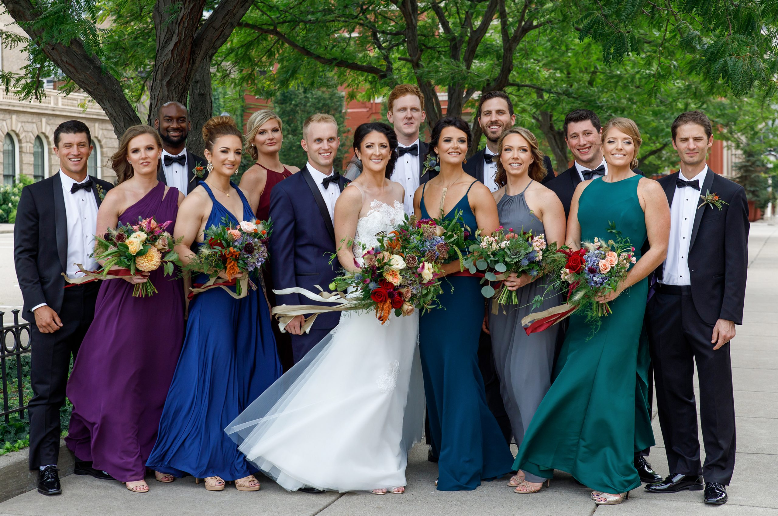 Colorful bridesmaids' dresses in a rich palette of purple, deep blue, crimson red, and teal are stunning with autumn field flowers of dahlias, roses, and hydrangea.