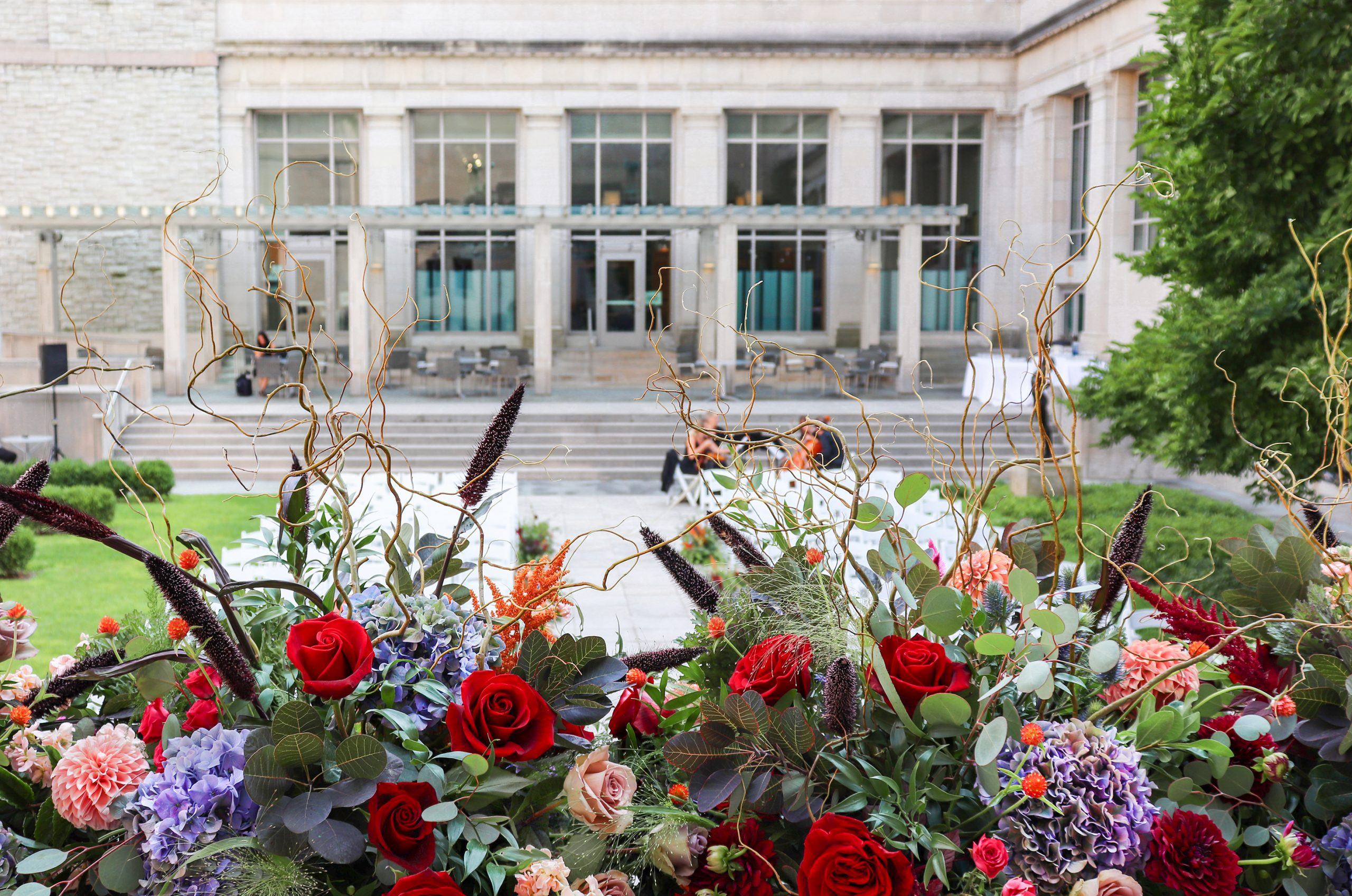 A courtyard view of colorful fall wedding flowers on the balcony at the historic Cincinnati Art Museum.