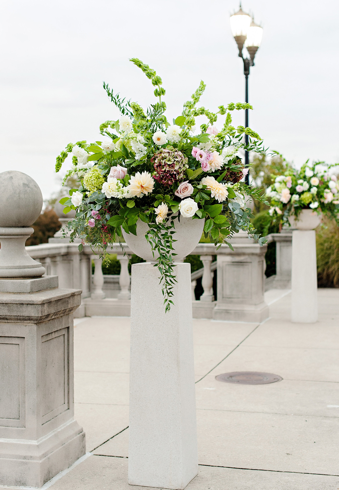 Lush, natural fresh ceremony flower arrangements in fall pastels, greens, crimson red and burgundy accents set on tall pedestals for an outdoor wedding at Cincinnati's Ault Park Pavilion.
