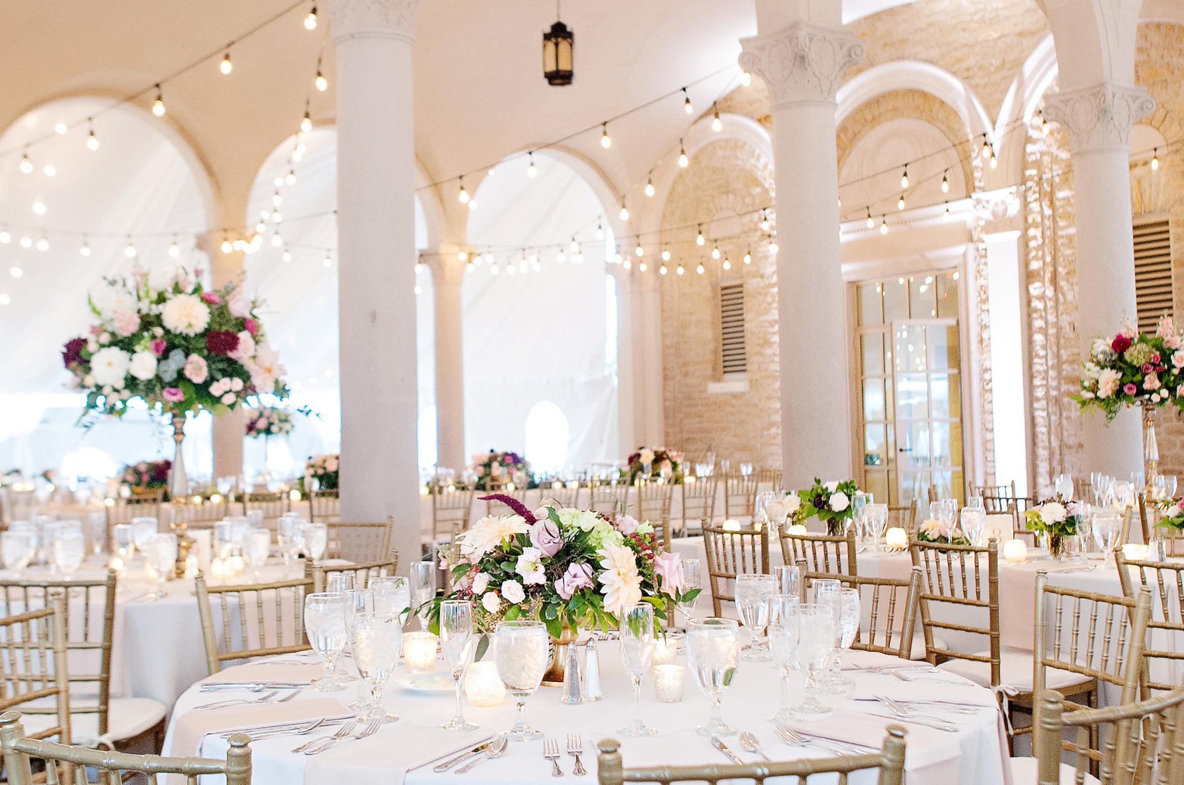 Pastel white, blush, pink, and burgundy fall wedding flowers for tented outdoor reception tables in the Ault Park Pavilion.