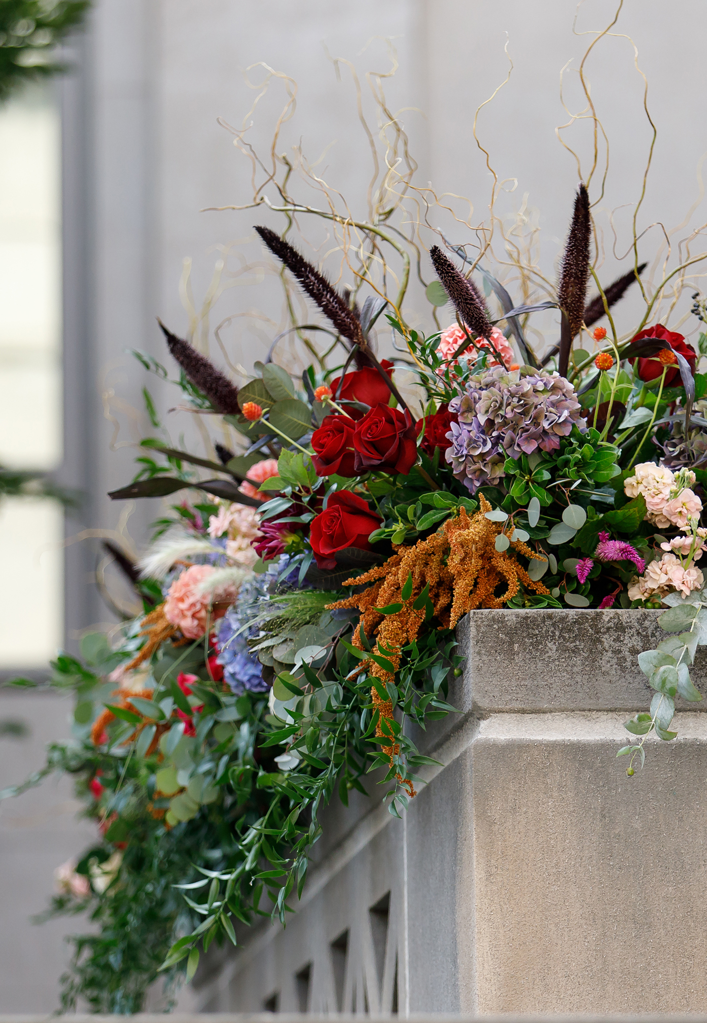 Fall wedding flowers in rich jewel tones designed as long arrangements for the outdoor ceremony balcony.
