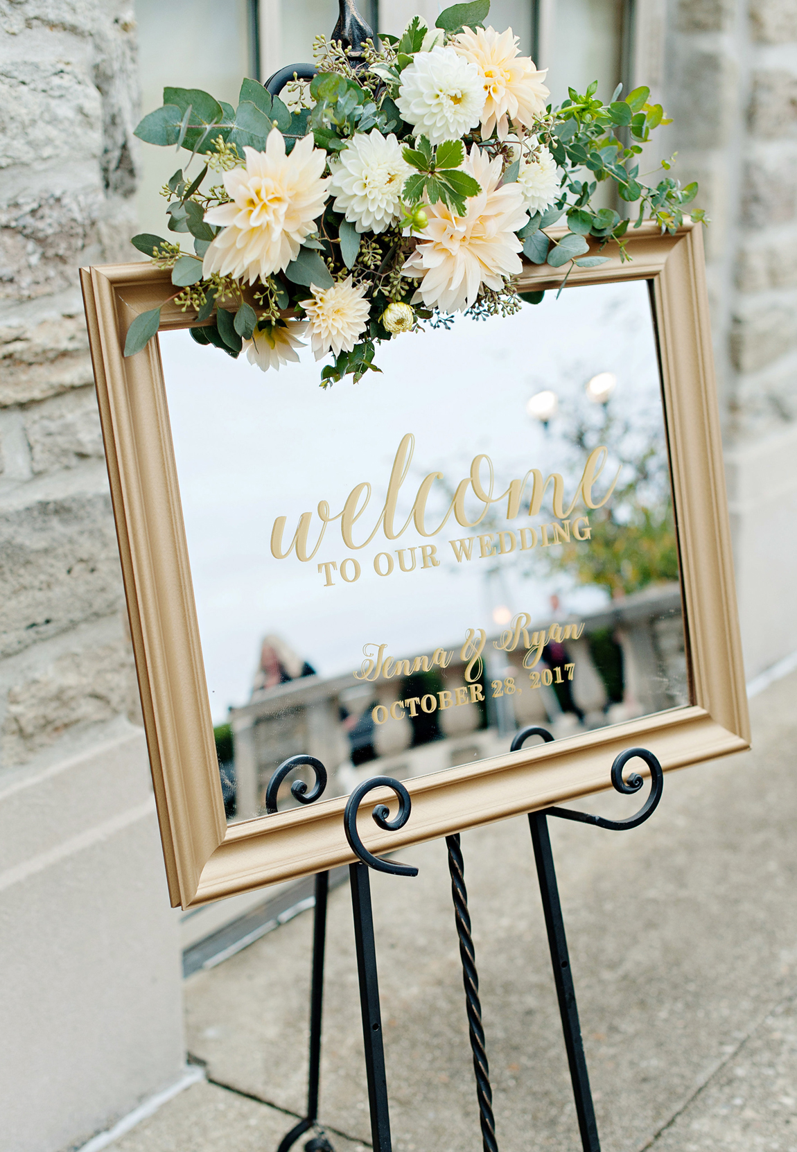 For an Ault Park outdoor wedding, guests are greeted by a mirrored gold framed Welcome sign dressed in fresh flowers with cafe-au-lait ivory and white dahlias