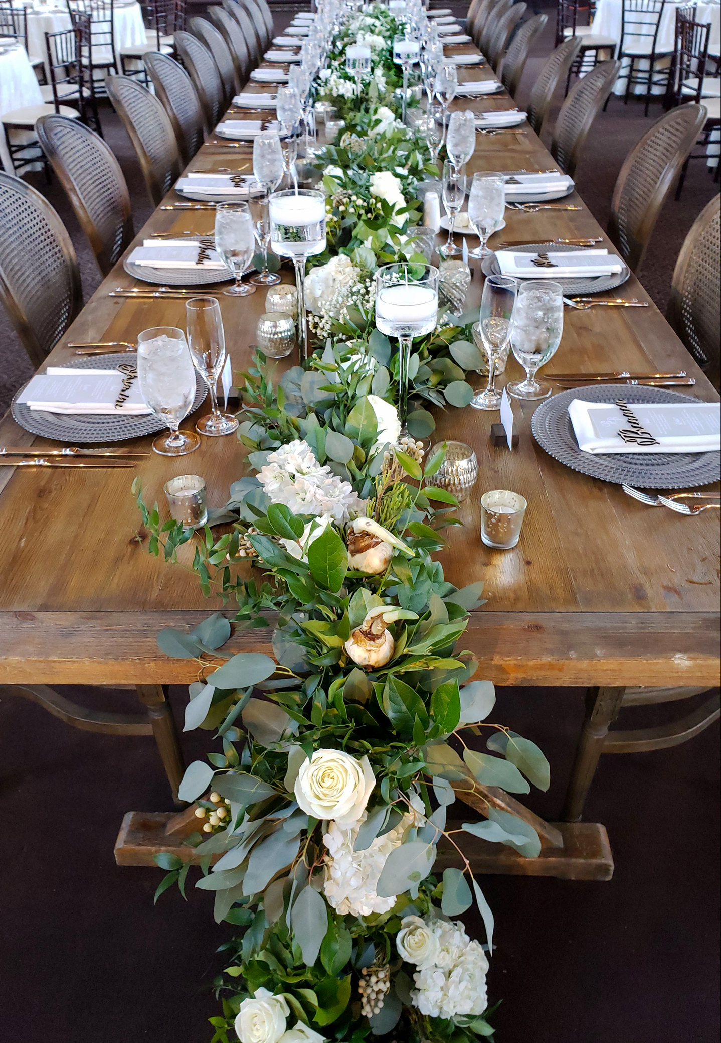 A long head table draped with white flowered lush green garland and set with dozens of candles.