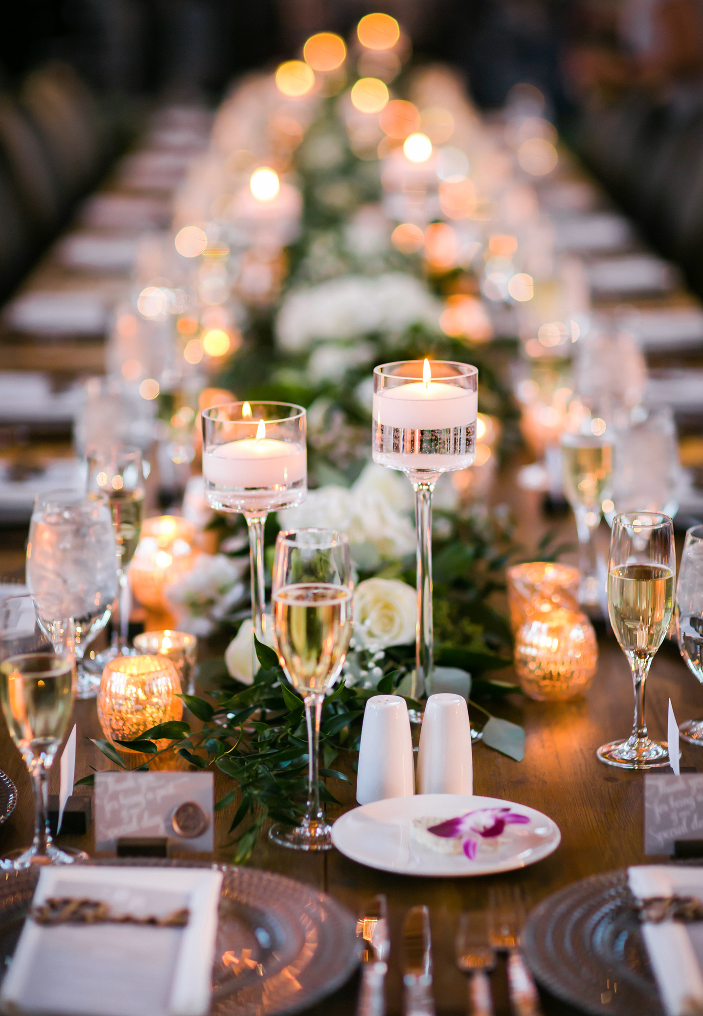 Lovely green garlands with white fresh spring flowers and dozens of candle votives and floating candle light on the head table for winter wedding decor.