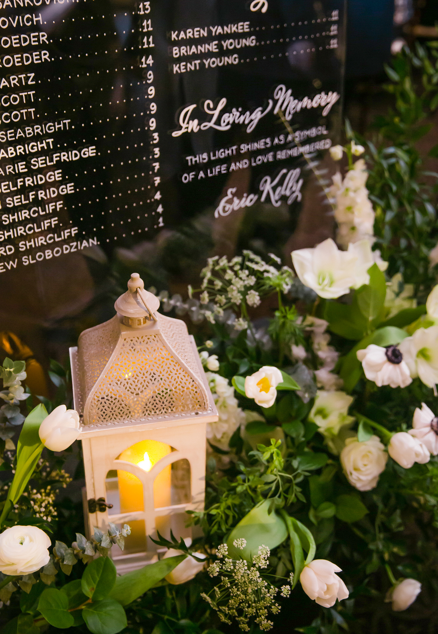 """Display """"In Loving Memory"""" vignette with standing sign and white and green ground flower arrangements with candle lantern"""