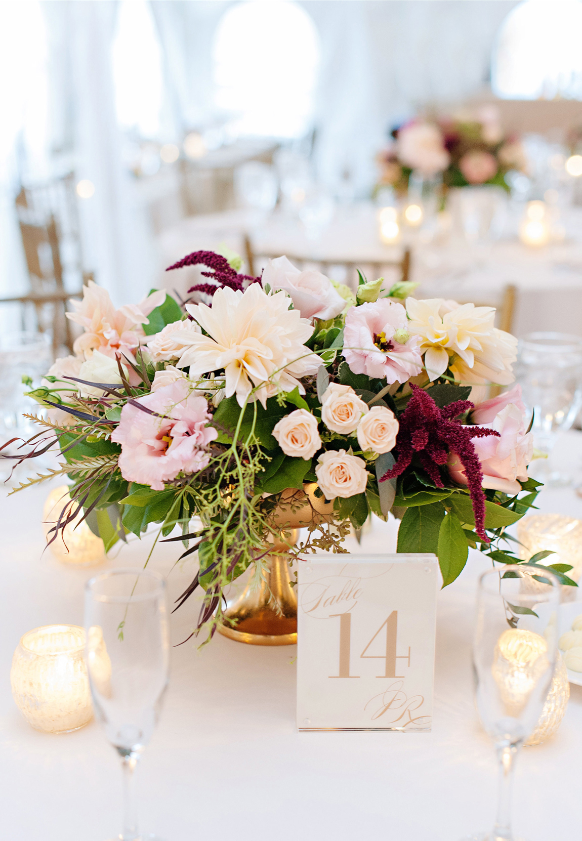 Low fresh flower wedding centerpiece in a gold pedestal with soft fall colors of white, blush, and pink with burgundy accents.