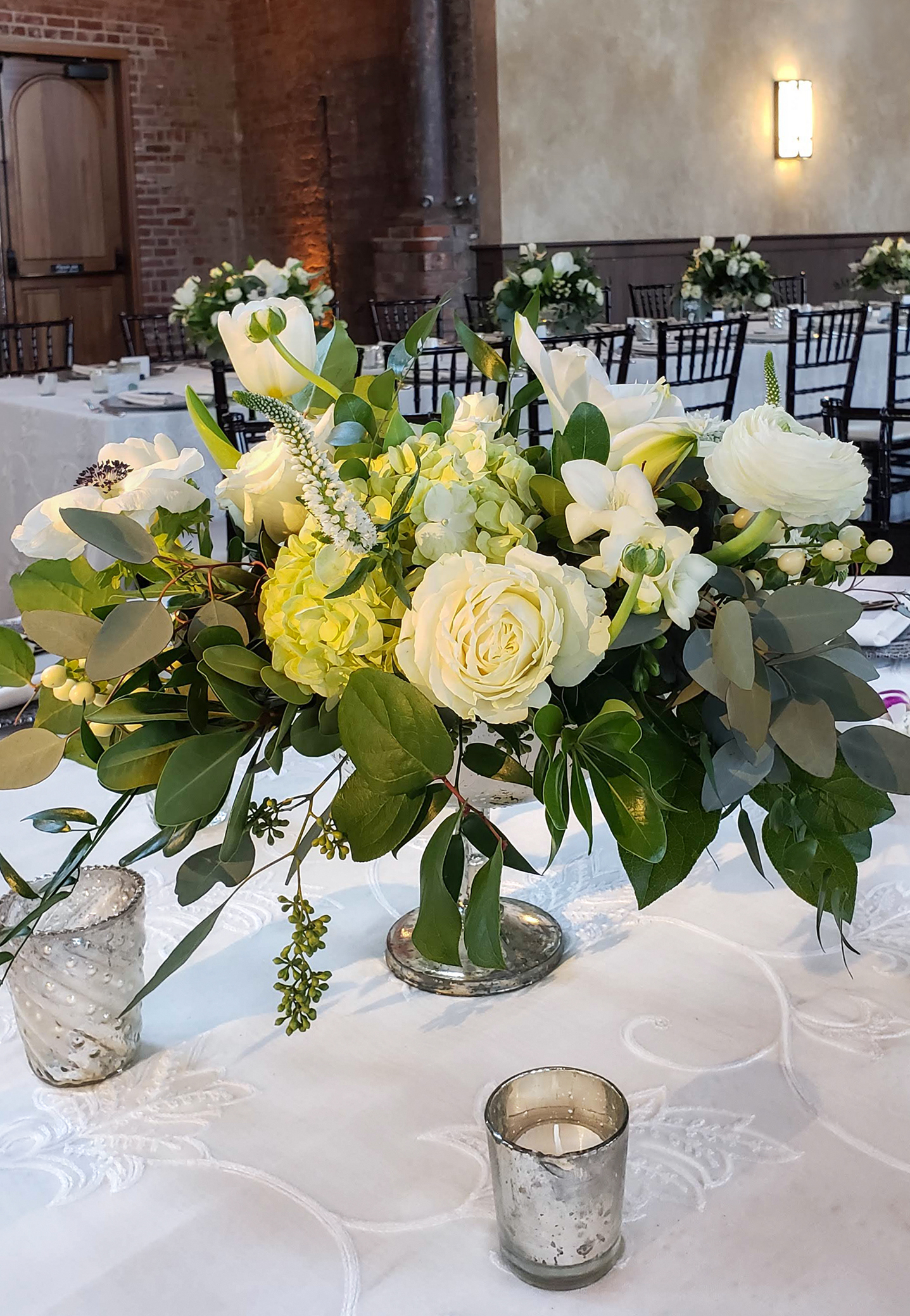 For a winter wedding at The Monastery, a classic neutral palette of white and green in a low and lush pedestal fresh spring flower centerpiece in a natural style.