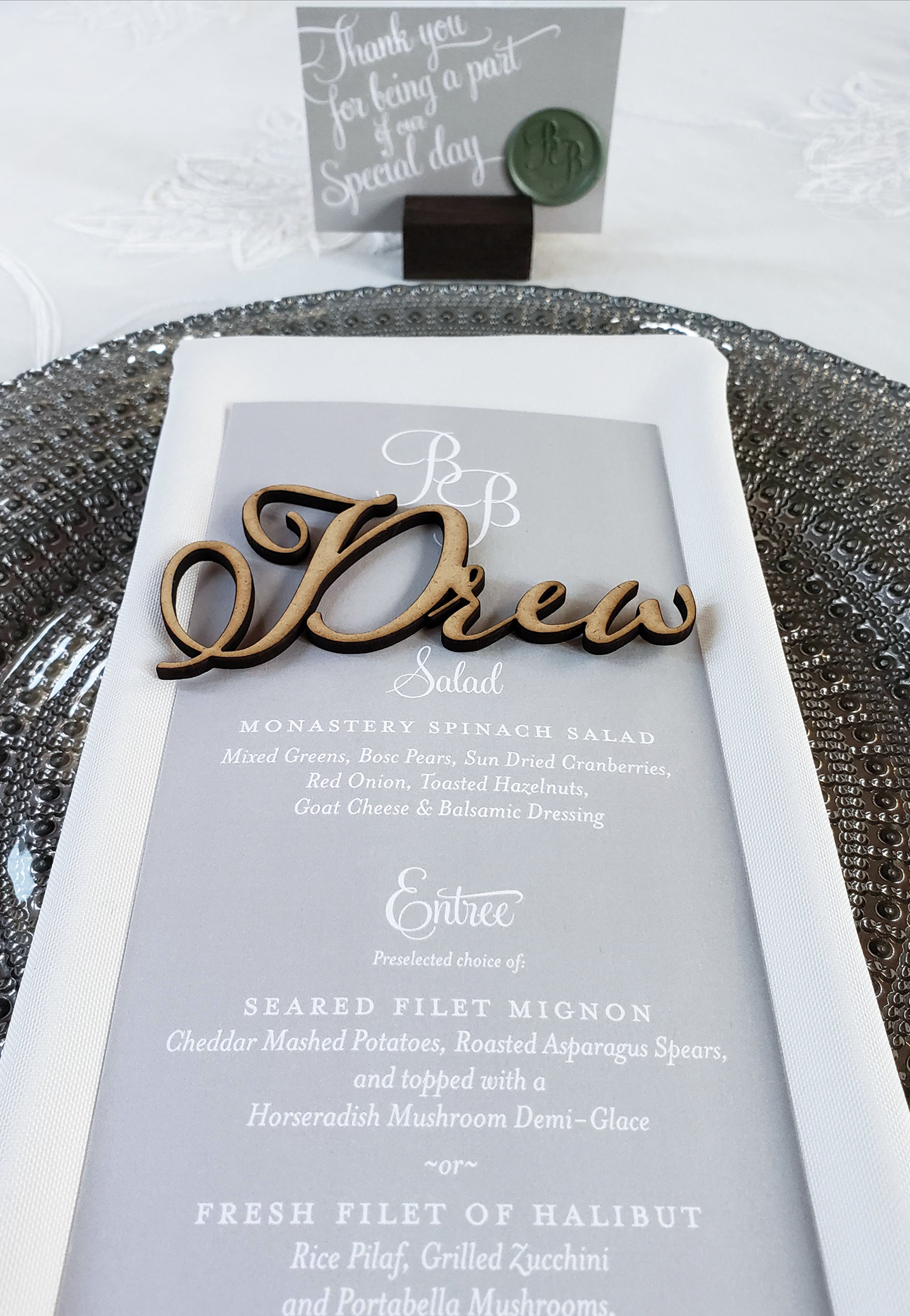 Handsome table settings with dark platinum glass chargers, calligraphy place cards, and laser cut script names for each guest at a chic winter wedding.