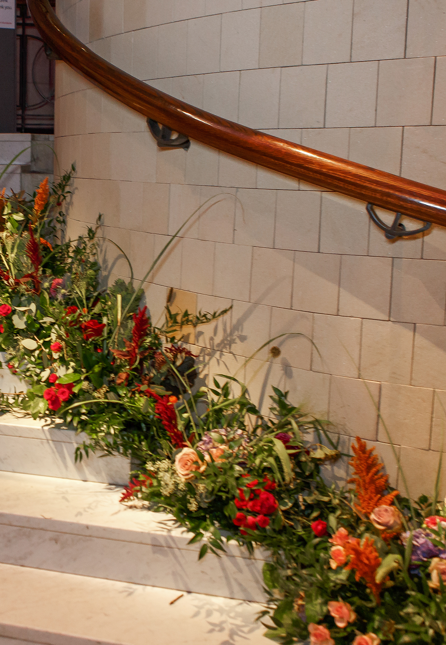 Garden stye natural floral arrangements in colorful autumn flowers lining the winding circular staircase in local wedding venue, the Cincinnati Art Museum.