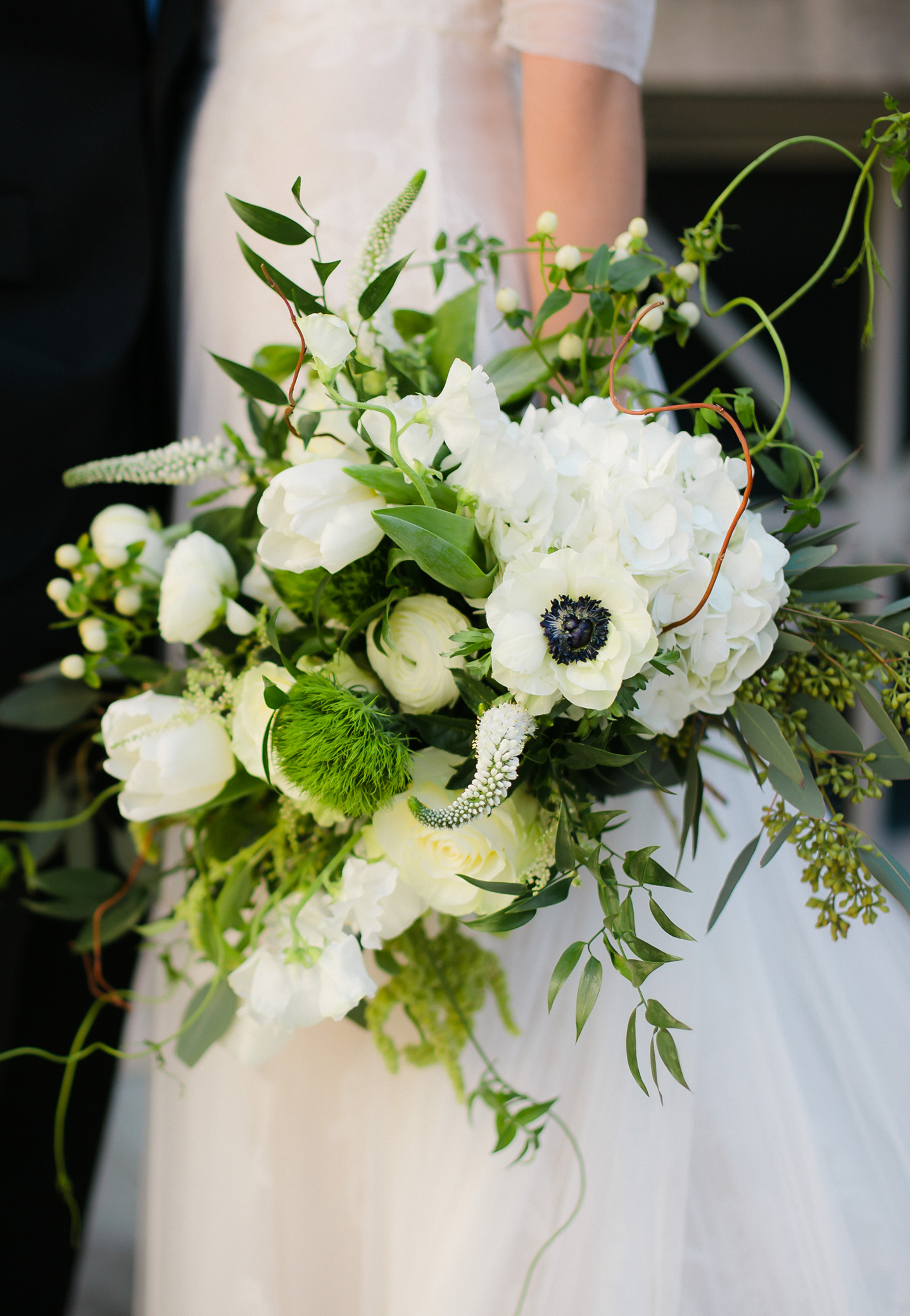 Spring bouquet in a natural organic shape with white tulips, anemones, lush foliage, and berries.