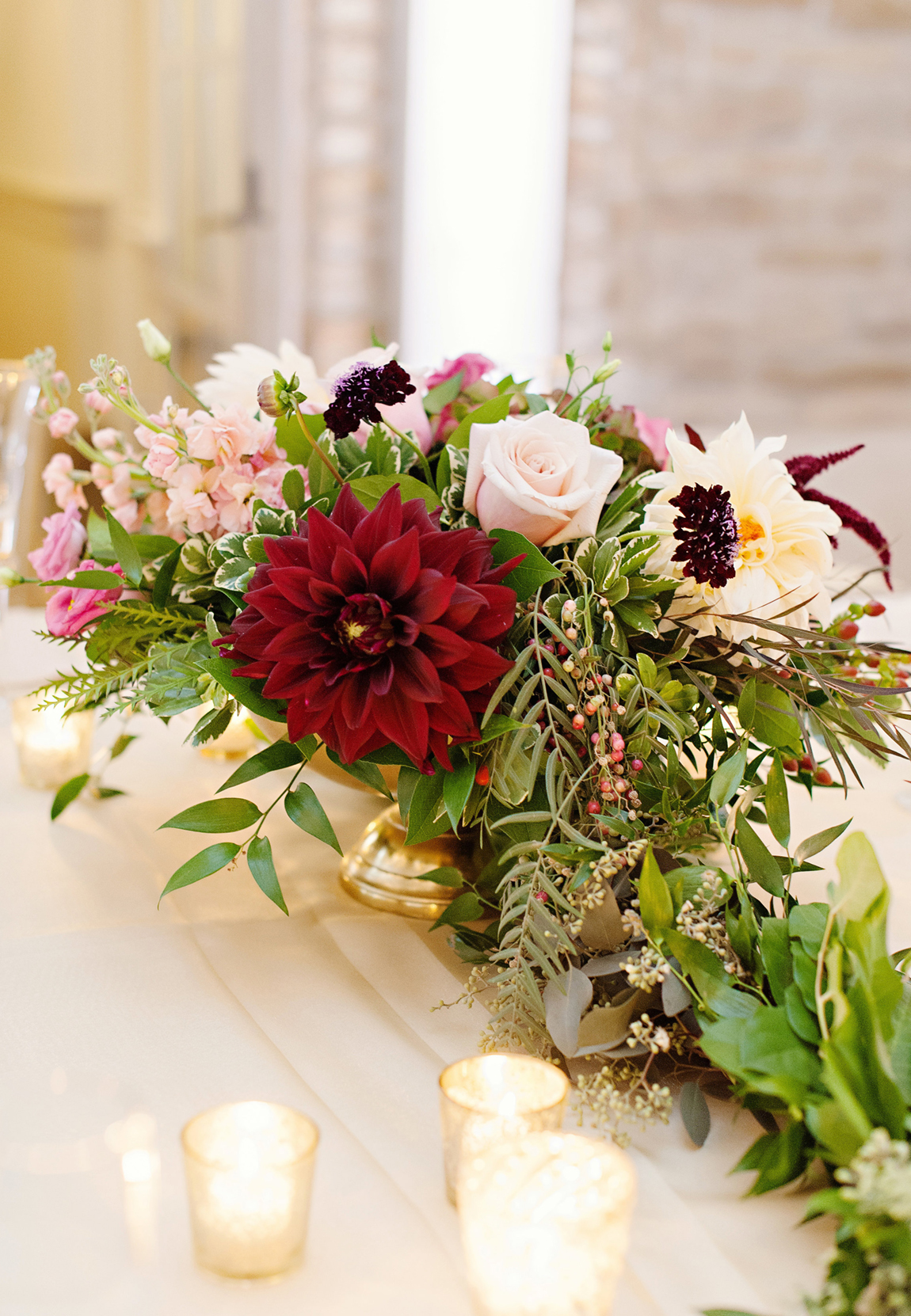 A low gold pedestal centerpiece with green garland for a unique head table at a tented outdoor wedding. Soft pastel fall flowers with burgundy and crimson accents and dahlias.