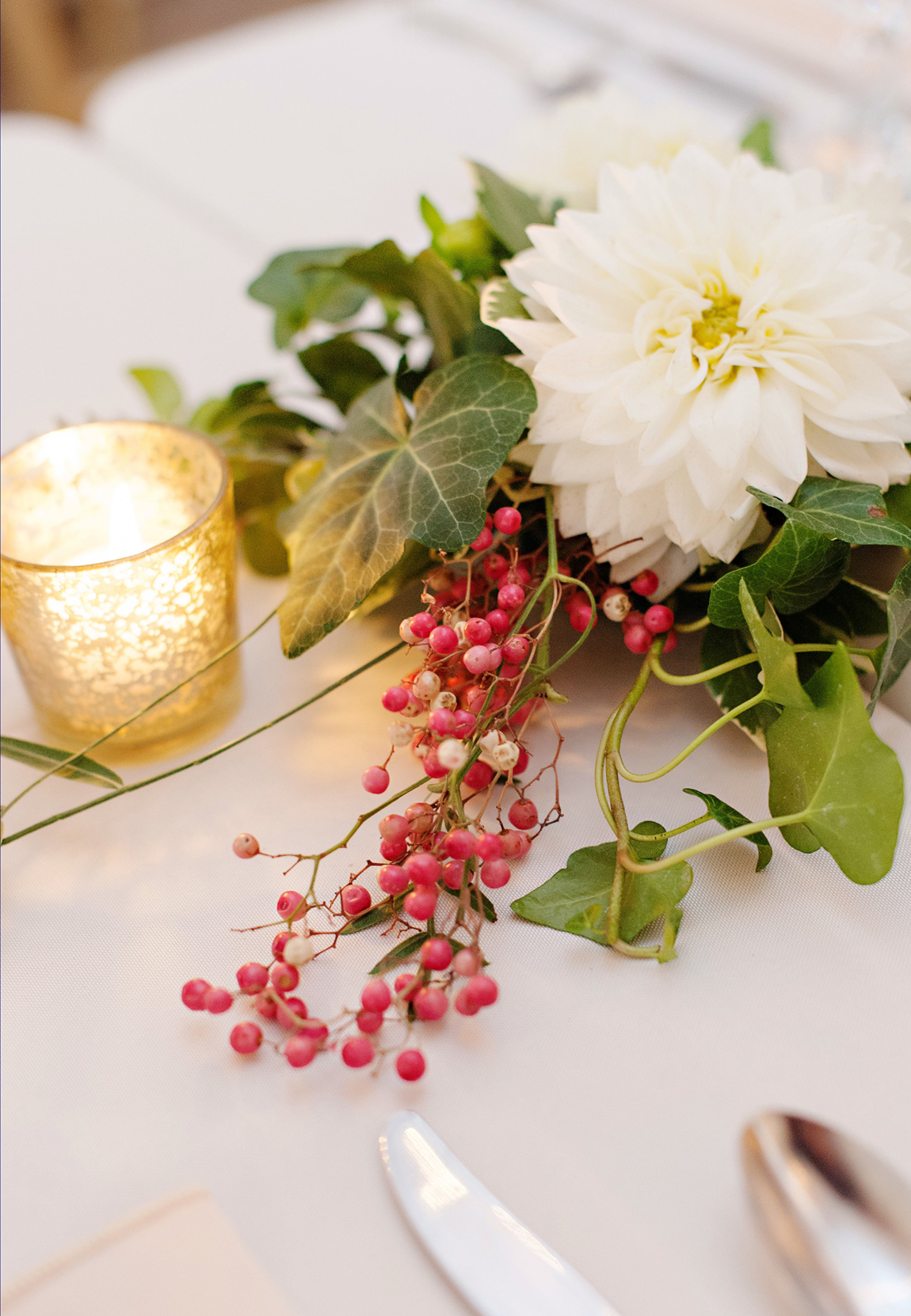 Flower fresh green garland with pink pepper berry accents and fall dahlia flowers on the head table at an outdoor park wedding.