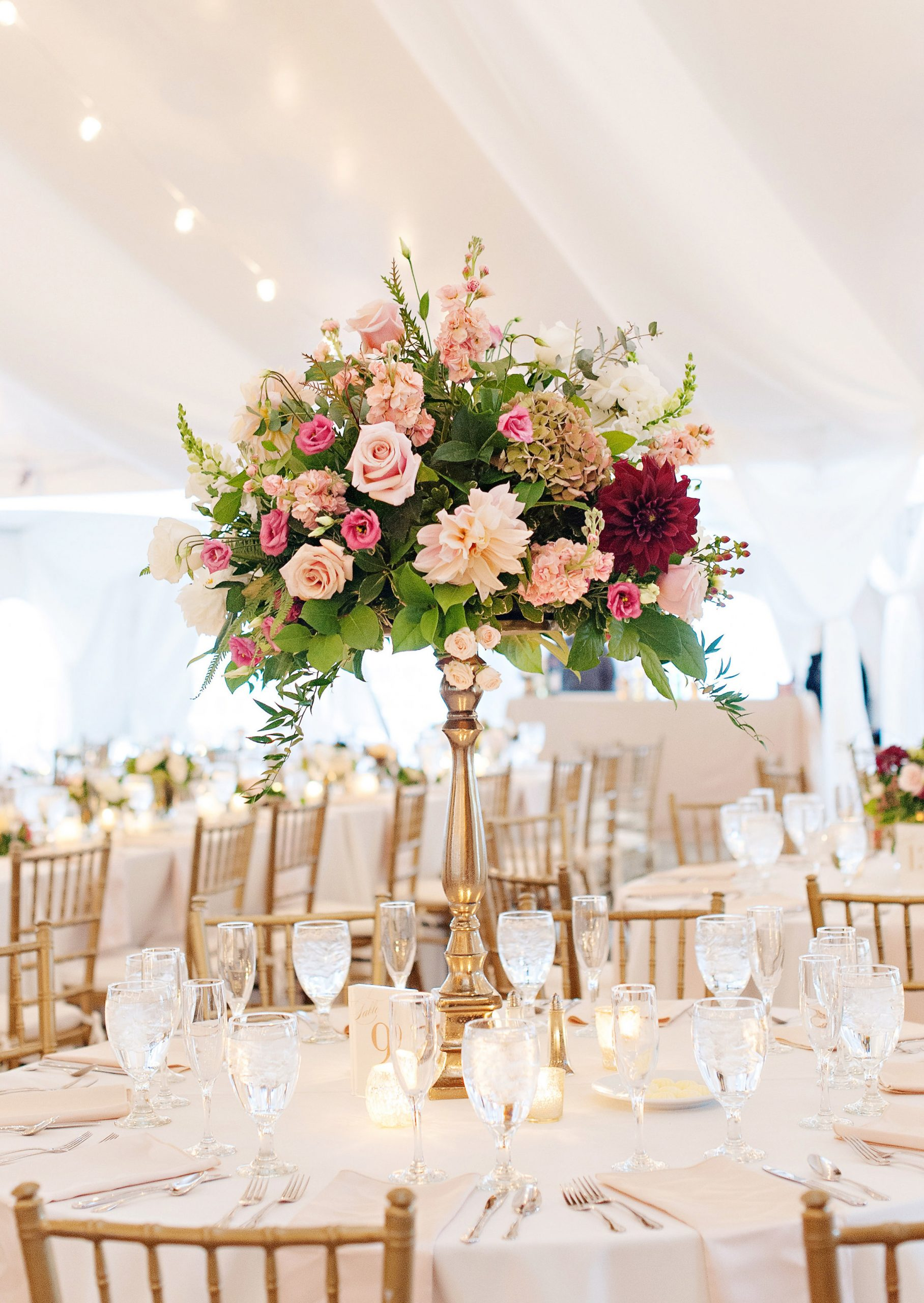 Striking tall wedding floral table centerpiece on a gold pedestal in fall pastel flowers of blush, pink, and burgundy accents. Light and airy tented outdoor park wedding.