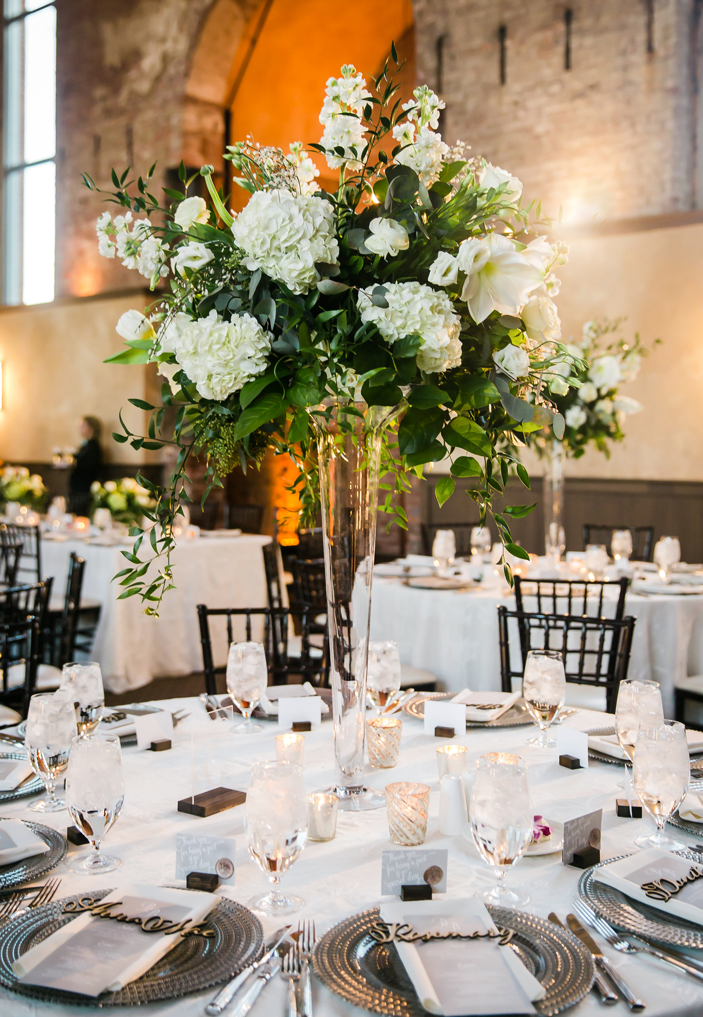 A tall classic white fresh flower centerpiece designed in a lush natural style sits on a glass riser at a winter wedding reception.