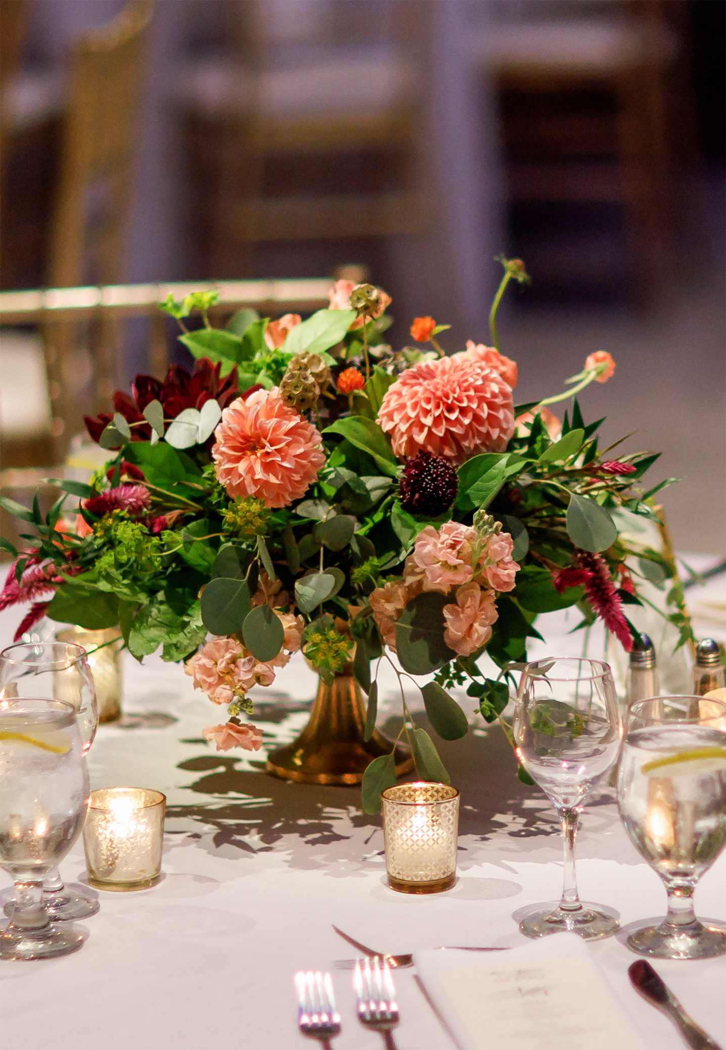 Autumn peach dahlia floral wedding centerpiece in a low-pedestal, designed in a soft natural style.