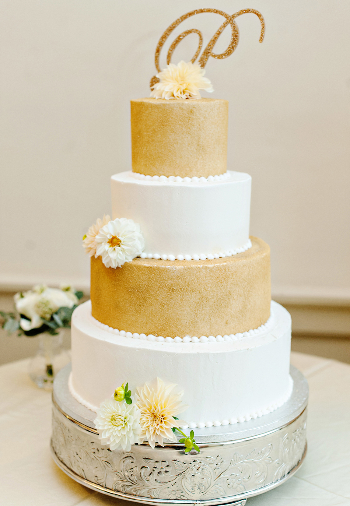 A pretty wedding cake with gold and white layers and soft autumn flowers.