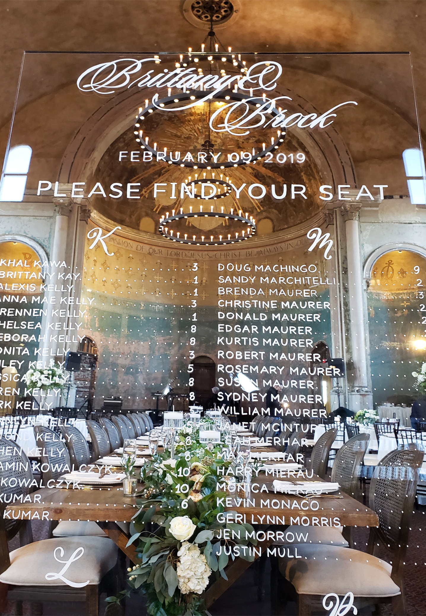 See-through, glass free-standing guest seating sign with white letters at Cincinnati wedding venue, The Monastery.