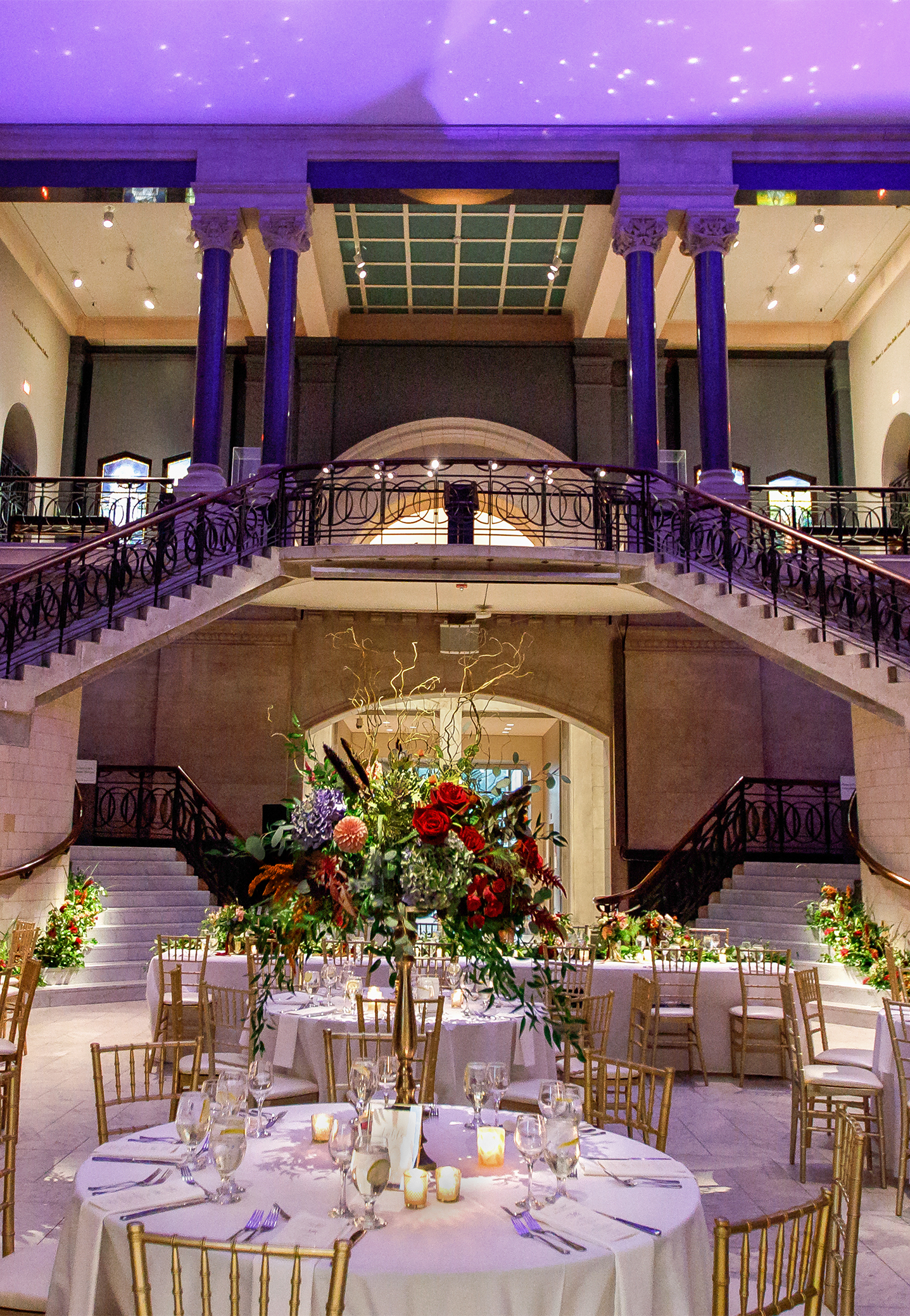 Fall wedding color in striking jewel tone floral tall and low centerpieces creates unique reception decor. Inspiration in fresh flowers and foliage set in the classic atrium architecture of the Cincinnati Art Museum wedding venue.