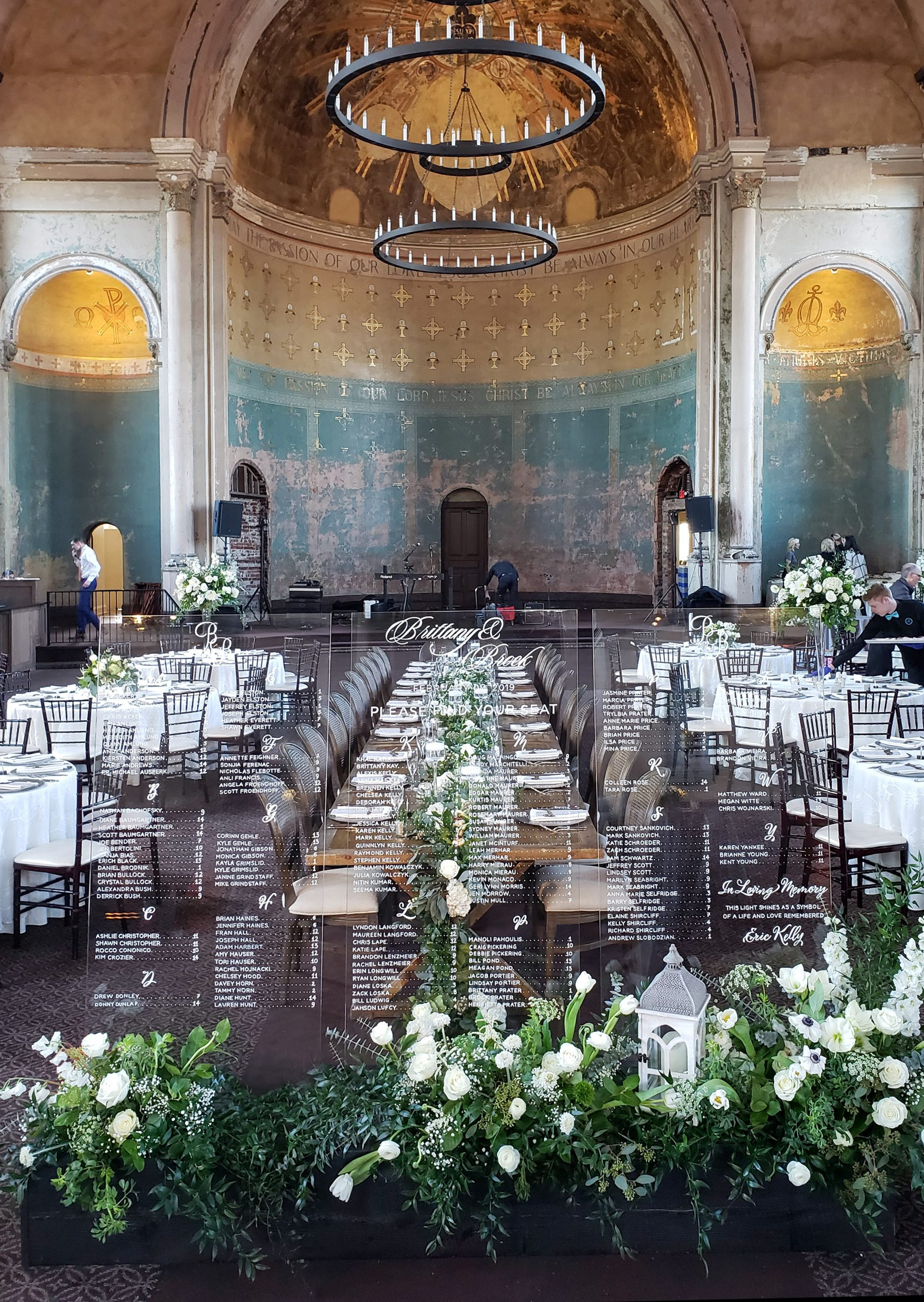 Display of fresh flower ground arrangements in white at the base of the free-standing glass setting signs that is a striking focal in the grand space of The Monastery.