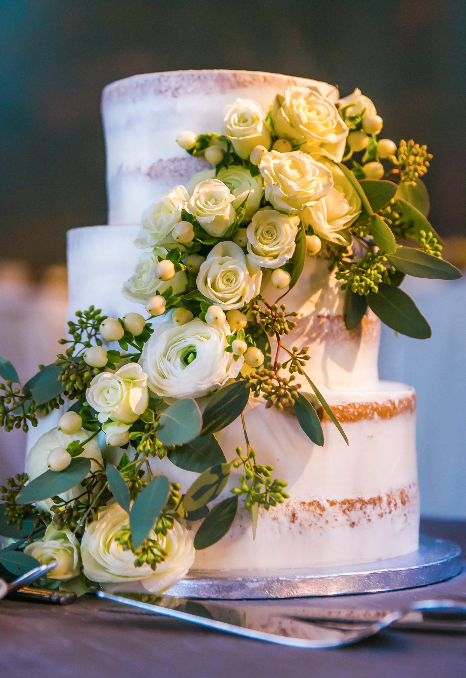 Lush fresh flowers and greens cascade down the layers of a naked cake in white.