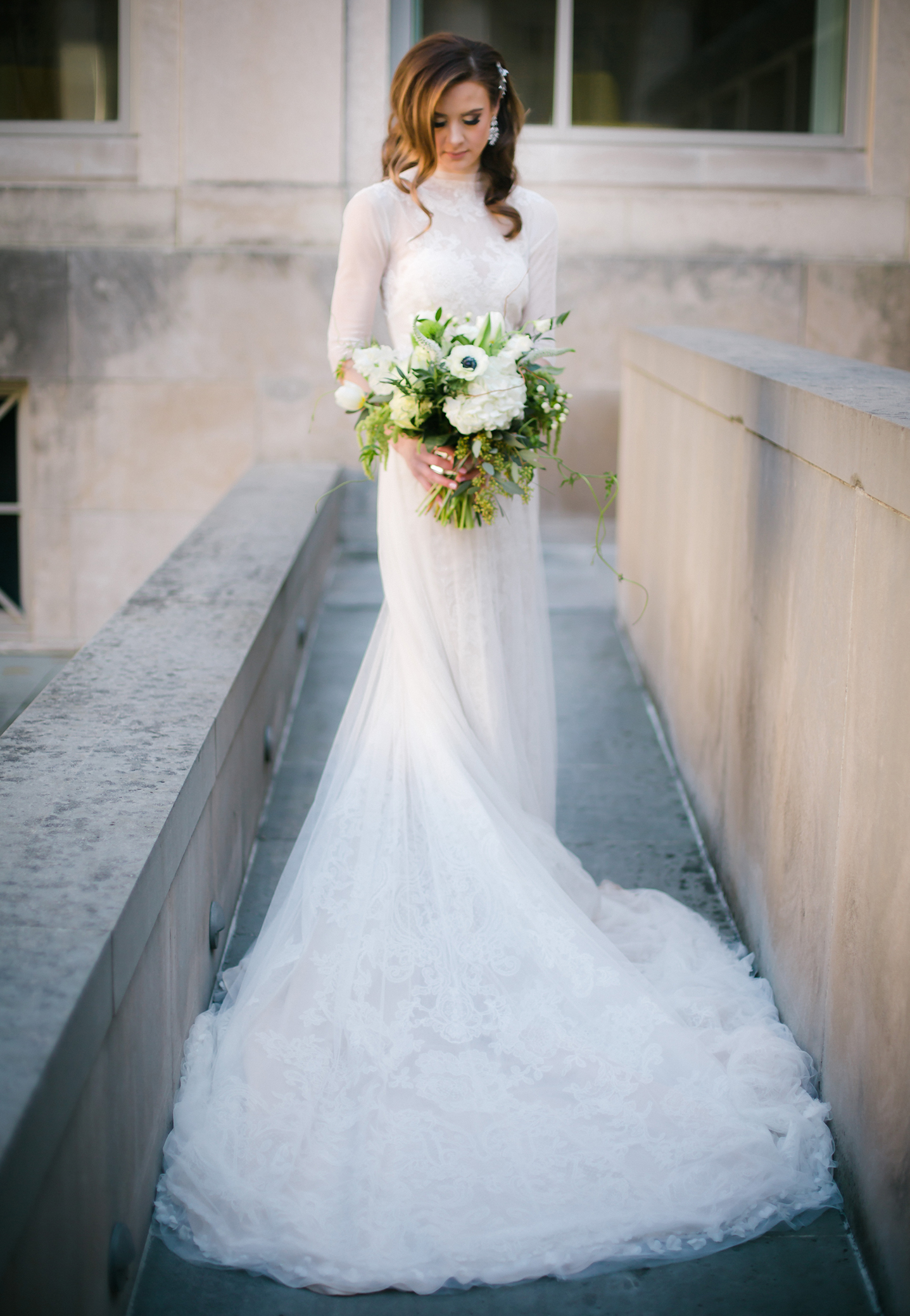 Winter bride in an elegant wedding dress holding a white and green bouquet in a natural organic shape.