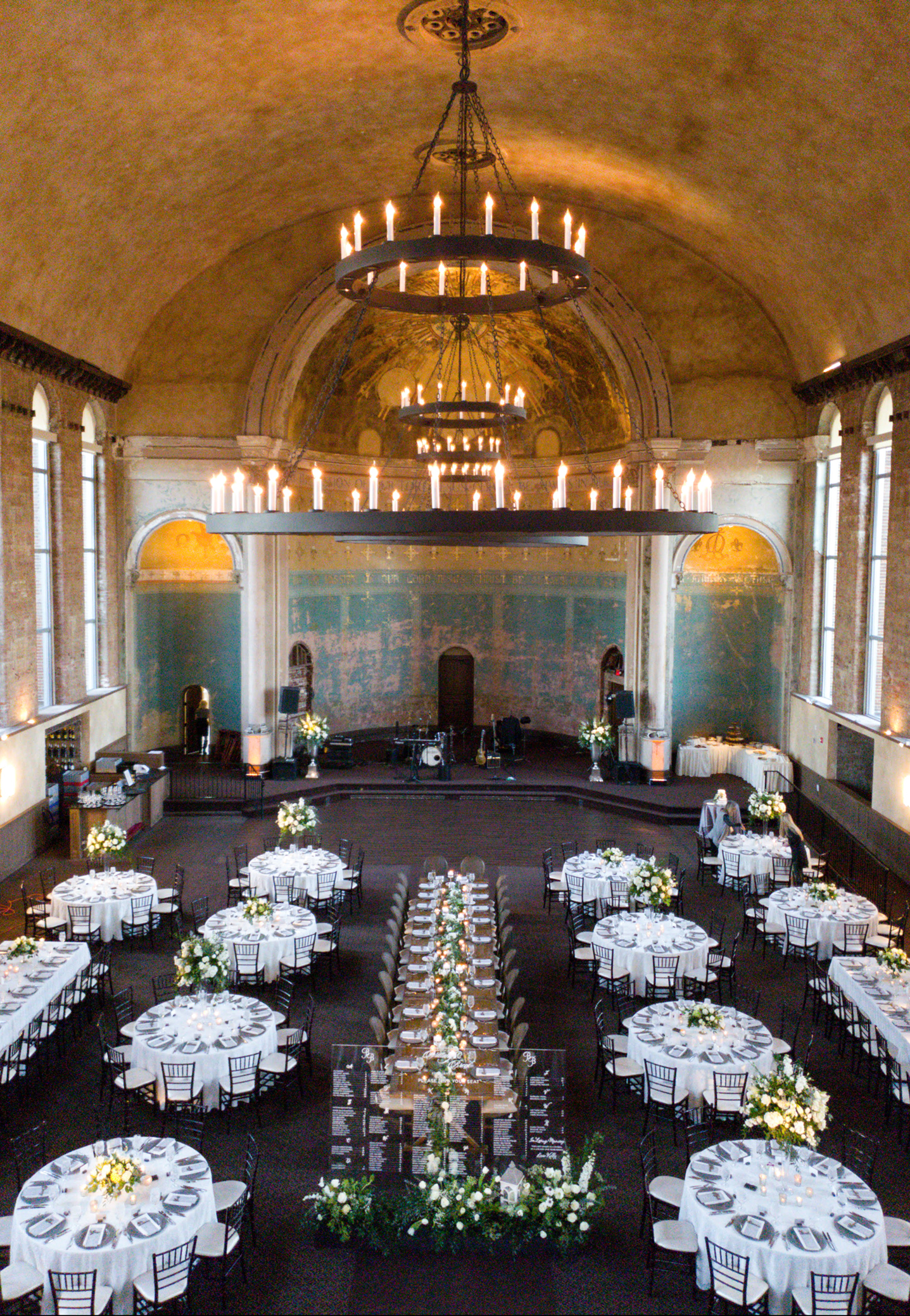 Classic white wedding tables and lush flowers fill the soaring space of The Monastery, a historic Cincinnati wedding venue.