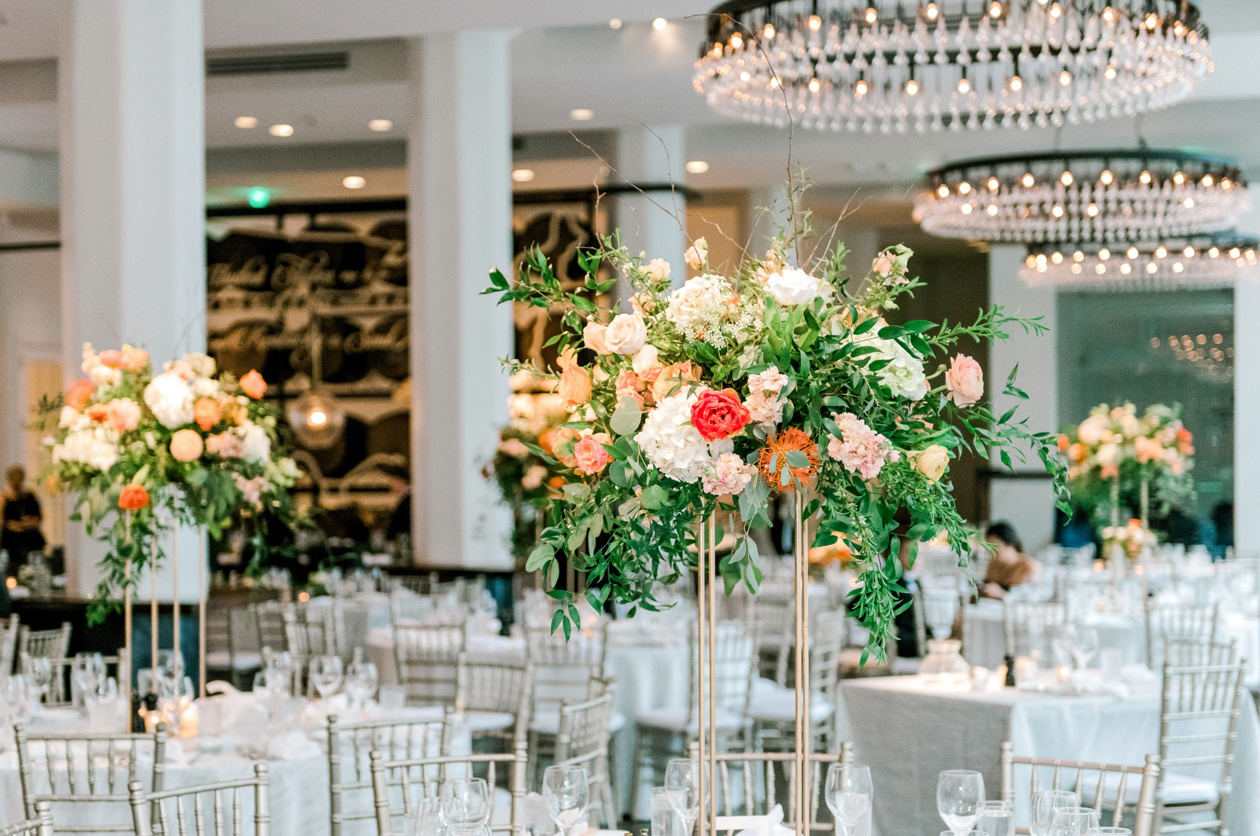 Elegant garden style tall floral centerpieces in white and peach spring flowers accented with bright orange tulips