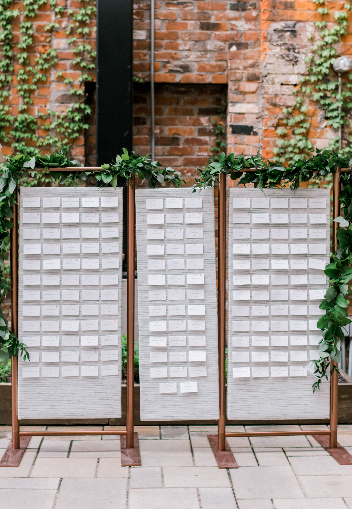 Uniquely made copper frames holding floating escort cards in a free standing display for a spring wedding in the courtyard of Hotel Covington.