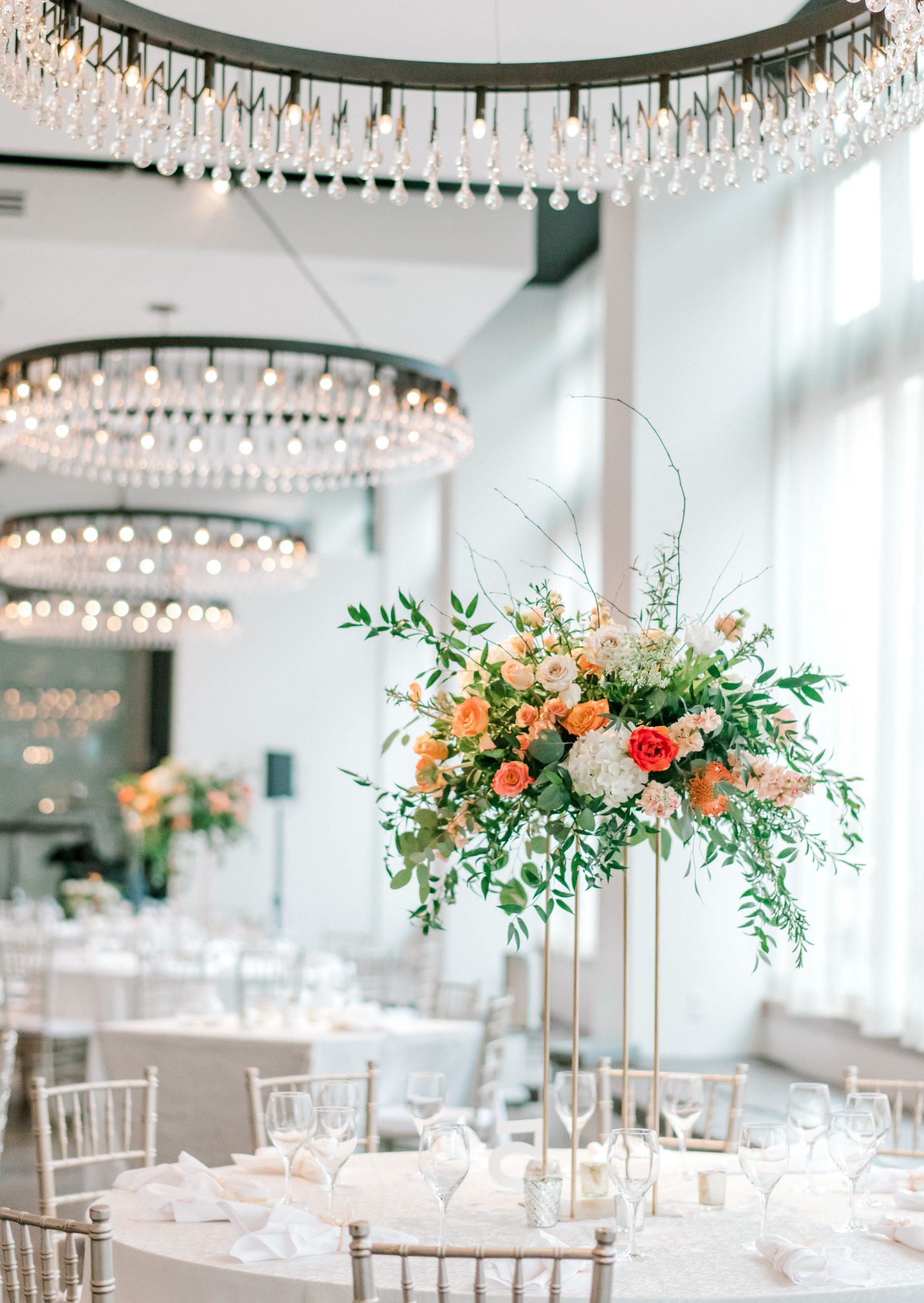Lush garden style centerpieces float on contemporary open risers above the tables for a chic wedding at Hotel Covington. Soft foliage and pastel spring flowers with vibrant tulips fill the unique florals.