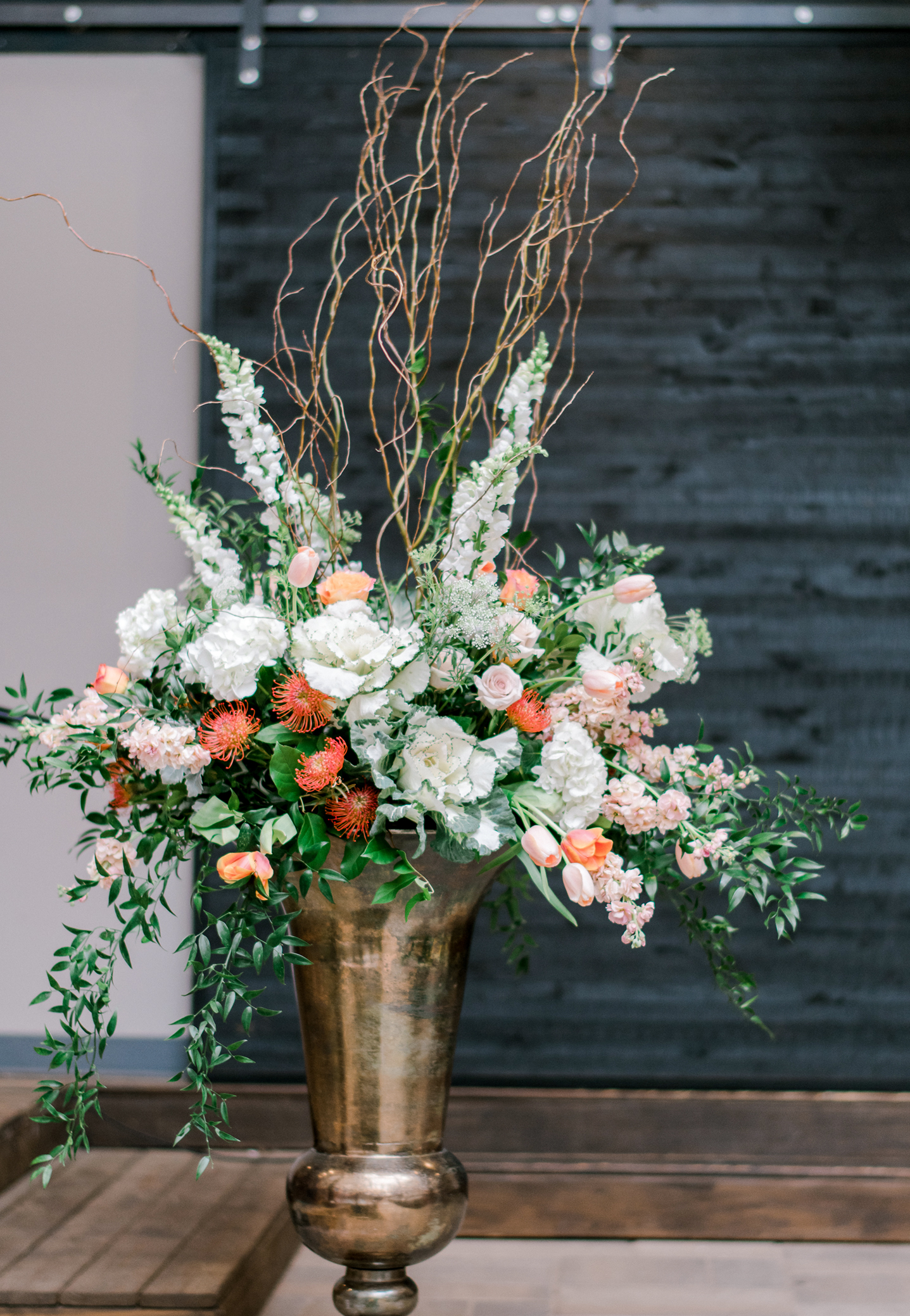 Unique wedding ceremony large scale floral arrangements in a spring palette of white, peach, green, with bright orange accents. Designed in massive bronze urns for a chic urban wedding.