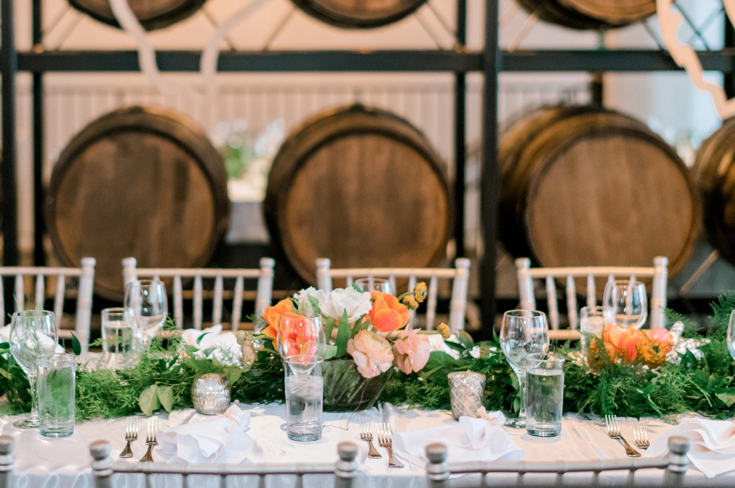 Fresh green garland of lush foliage and ferns mixed with spring flowers create a beautiful table runner for a chic wedding reception at Hotel Covington.
