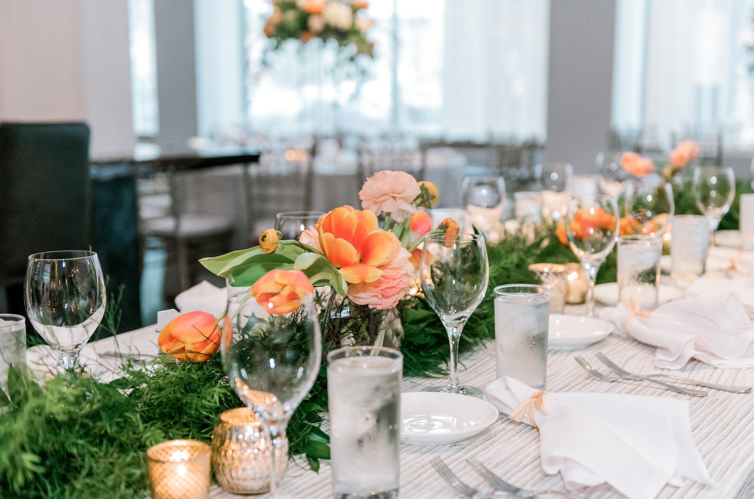 Lush green garland mixed with peach spring tulips and ranunculus flowers create low centerpiece tablescapes on wedding reception tables.