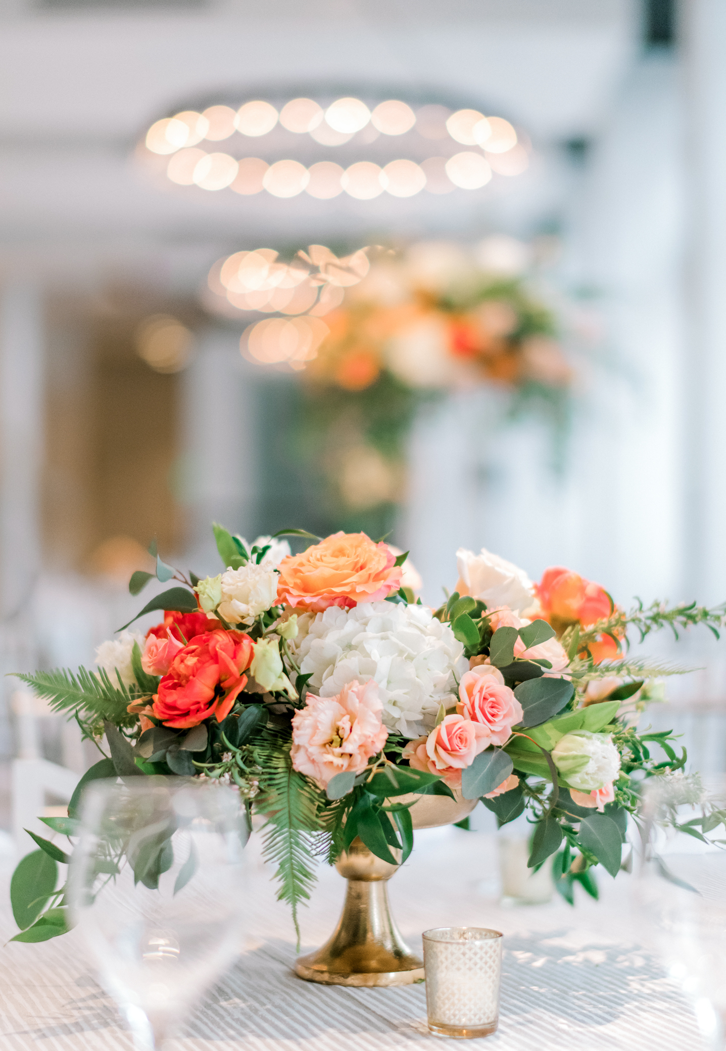 Low centerpiece in a soft natural style with a pretty mix of spring flowers in pastel blush, peach, and white, accented by bright orange tulips.