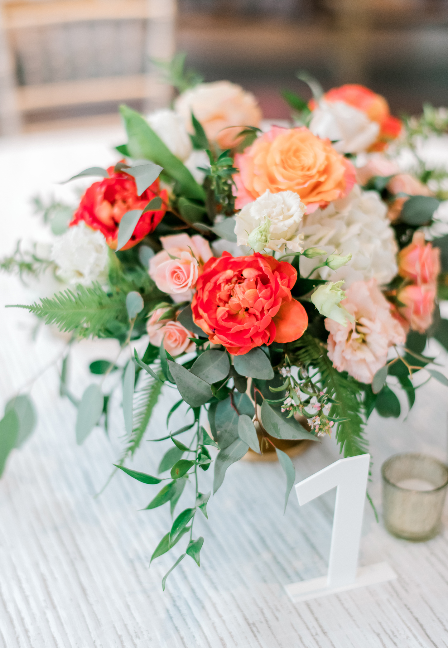 Garden style bright, lush flowers in a low pedestal centerpiece with double tulips for a spring wedding.