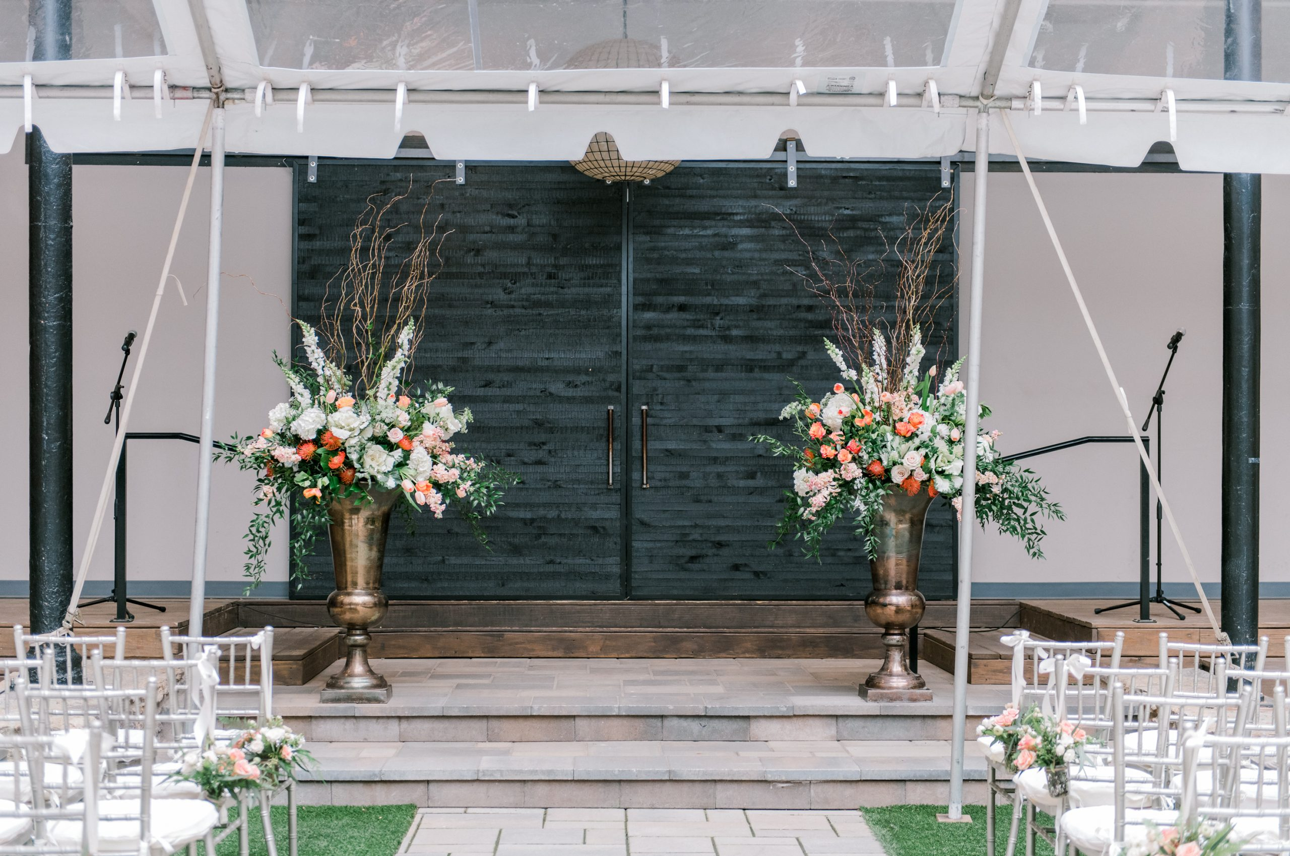 Large scale lush ceremony florals designed in massive bronze urns with white, peach, and green blooms, accented by bold orange flowers.