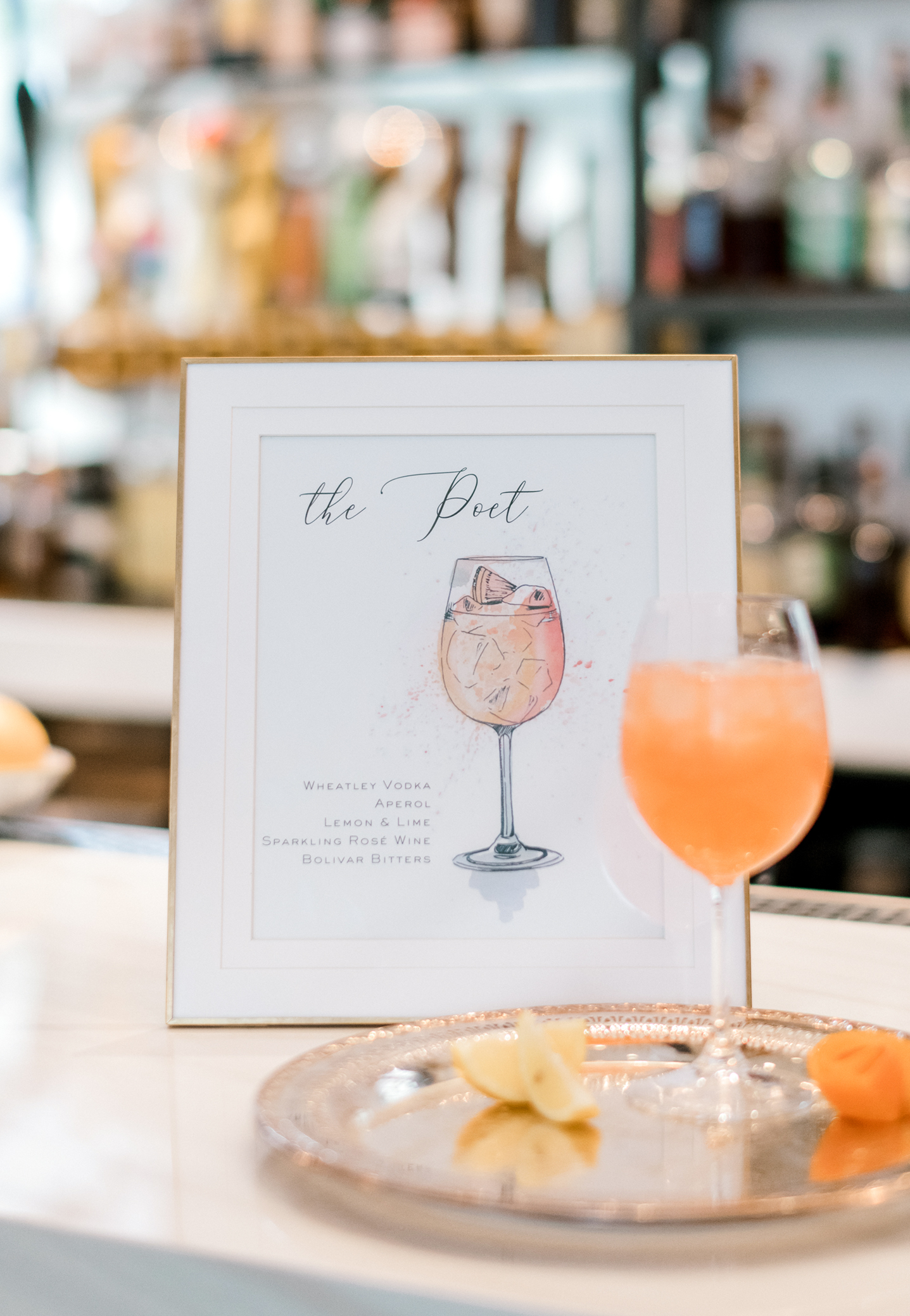 Pretty peach theme in a signature cocktail for a palette of pastel peach, white, green, and bright orange in a spring wedding.