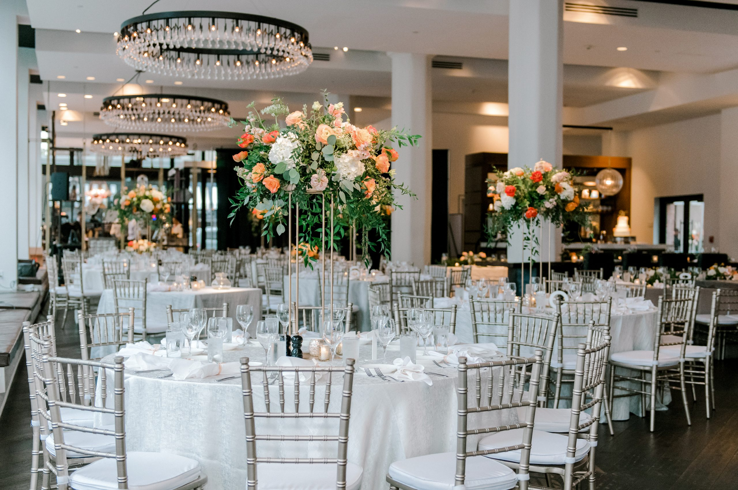 Tall centerpieces in a natural style with mixed foliage and spring flowers for a chic urban wedding reception at Hotel Covington.